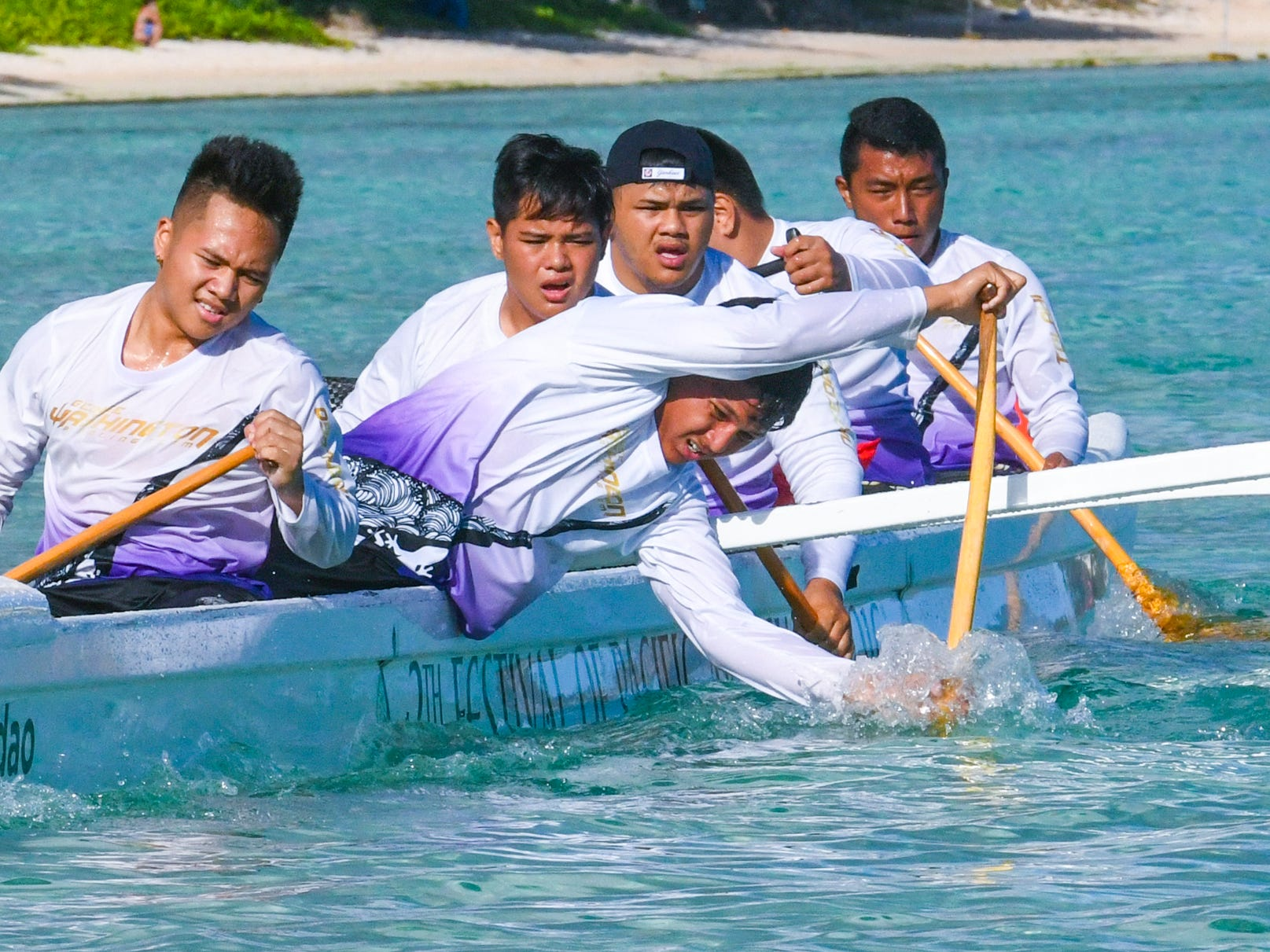 Paddlers from George Washington High School push their canoe through the waters off Matapang Beach as they compete against other teams in IIAAG Paddling competition preliminary races in Tumon on Saturday, May 11, 2019.