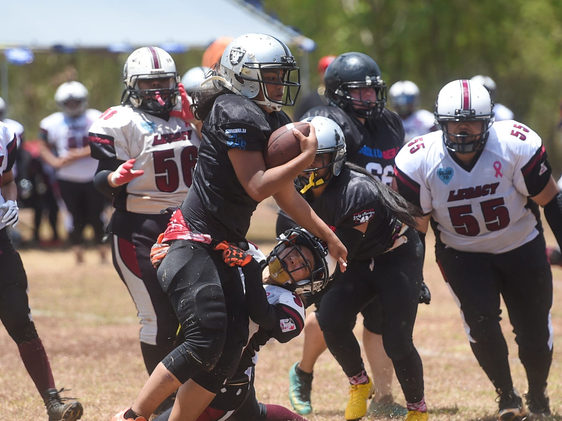 Sindalu/Raiders player Leticia Blas attempts to break a tackle against Legacy's Kaylani Plain Cruz during their 2019 Bud Light GWTFL game at the University of Guam Field in Mangilao, May 11, 2019. Legacy came away with a 20-0 victory for their second game of the season.