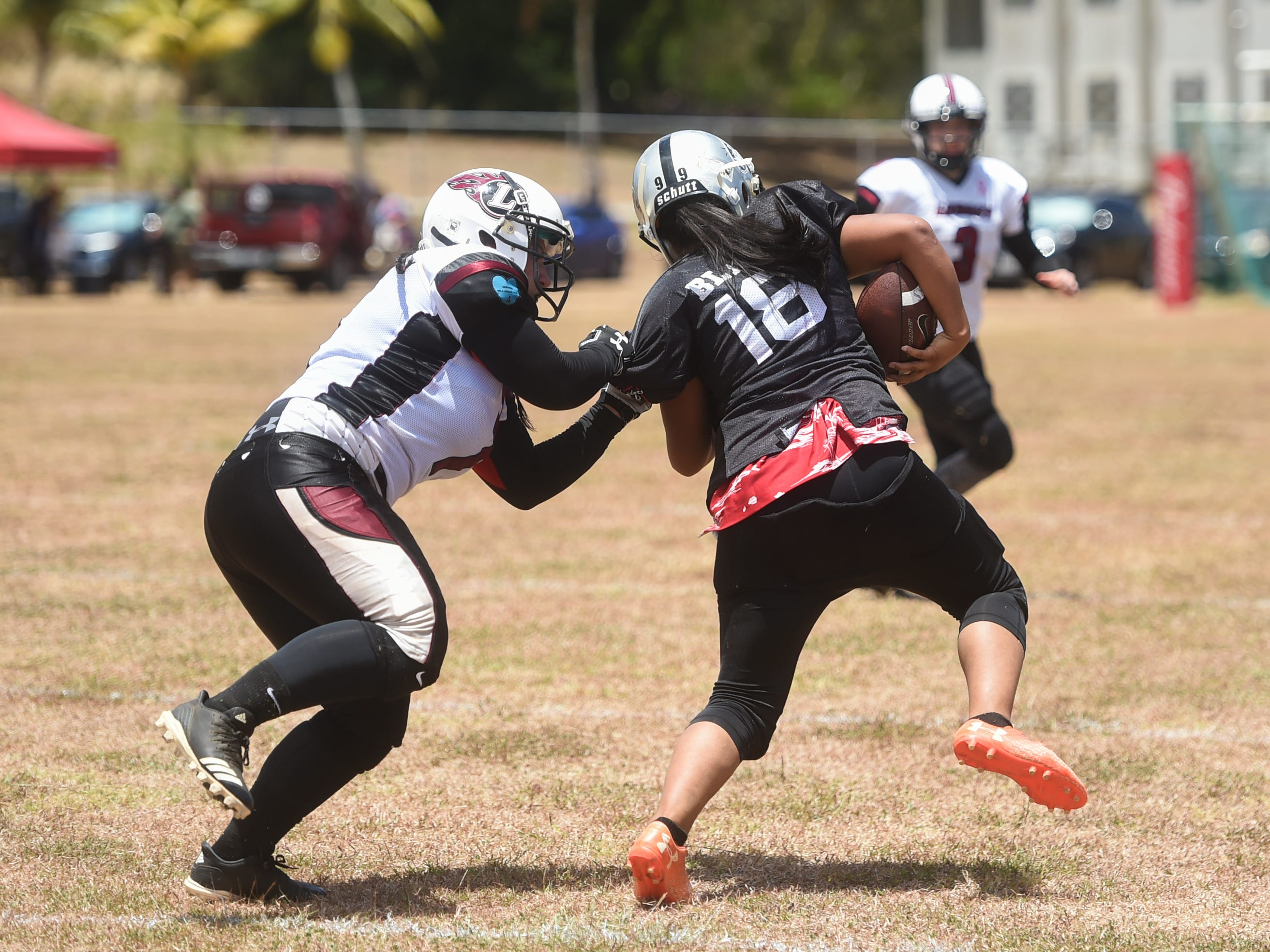 Sindalu/Raiders' Leticia Blas (18) is grabbed by Legacy's Ashley Arceo during their 2019 Bud Light GWTFL game at the University of Guam Field in Mangilao, May 11, 2019. Legacy came away with a 20-0 victory for their second game of the season.