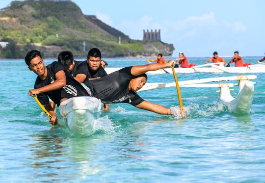 Simon Sanchez Shark paddlers power their way into a turn during a 1000m mixed manhoben preliminary race in IIAAG Paddling competition at Matapang Beach in Tumon on Saturday, May 11, 2019.
