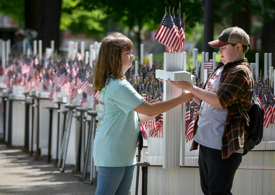 Daniel Lancaster, right, hands Libby Butler, both 13 years-old, an arm load of crosses as North Middle School students help erect, in Central Park, more than 5,000 crosses honoring Henderson County veterans, Thursday May 9, 2019.