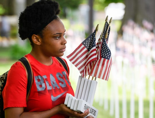 North Middle School student Jasmine Satcher, 14 years-old, carries an armload of crosses as the students help erect more than 5,000 crosses honoring Henderson County veterans, Thursday May 9, 2019.