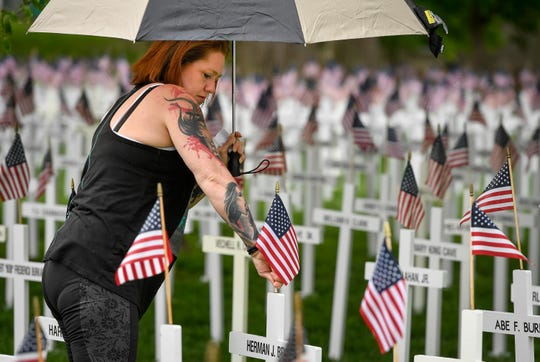WARM Center resident, Tonya Nickson checks and straightens flags adorning the more than 5,000 crosses erected in Central Park, each with the name of a deceased Henderson County veteran, Thursday May 9, 2019.