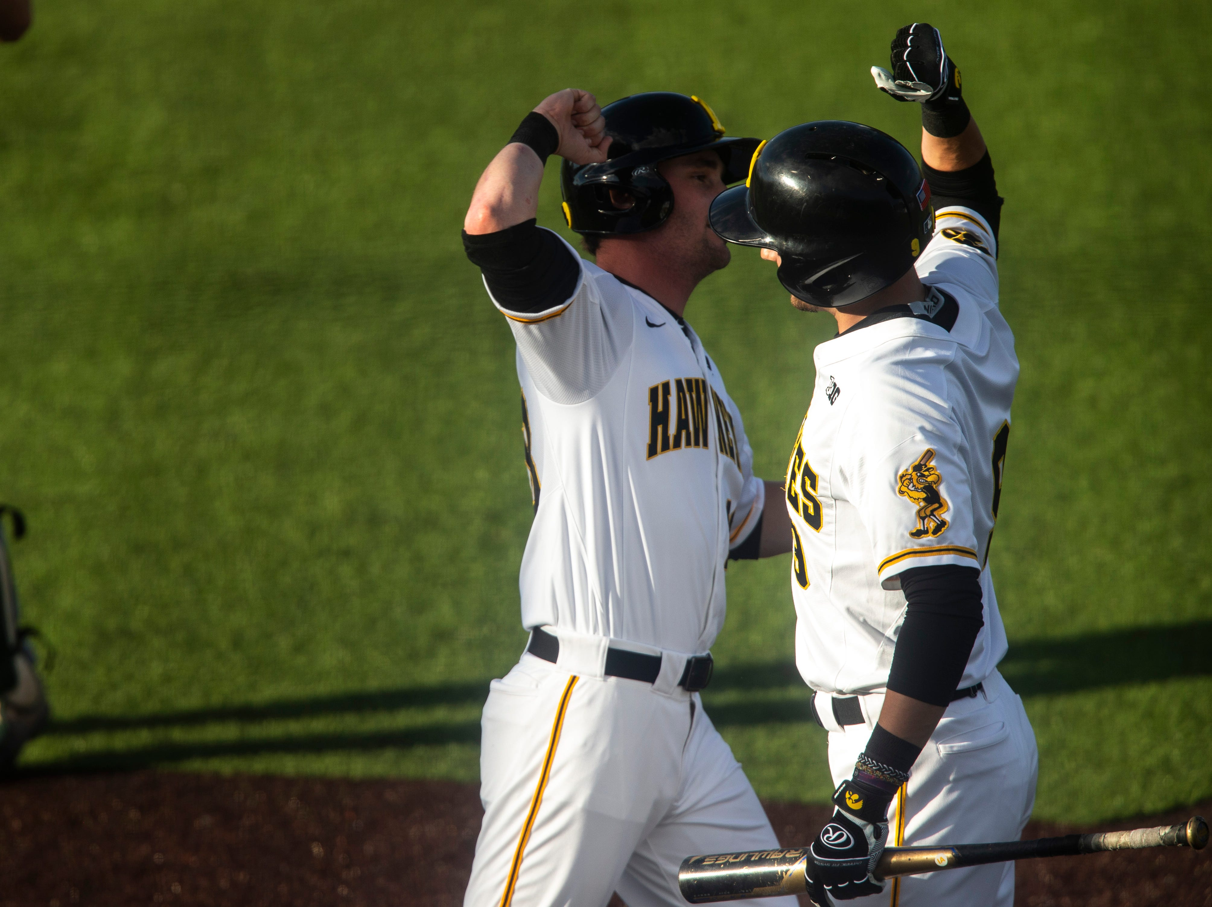 Iowa's Chris Whelan, left, celebrates with teammate Ben Norman after scoring a run during a NCAA Big Ten Conference baseball game, Friday, May 10, 2019, at Duane Banks Field on the University of Iowa campus in Iowa City, Iowa.