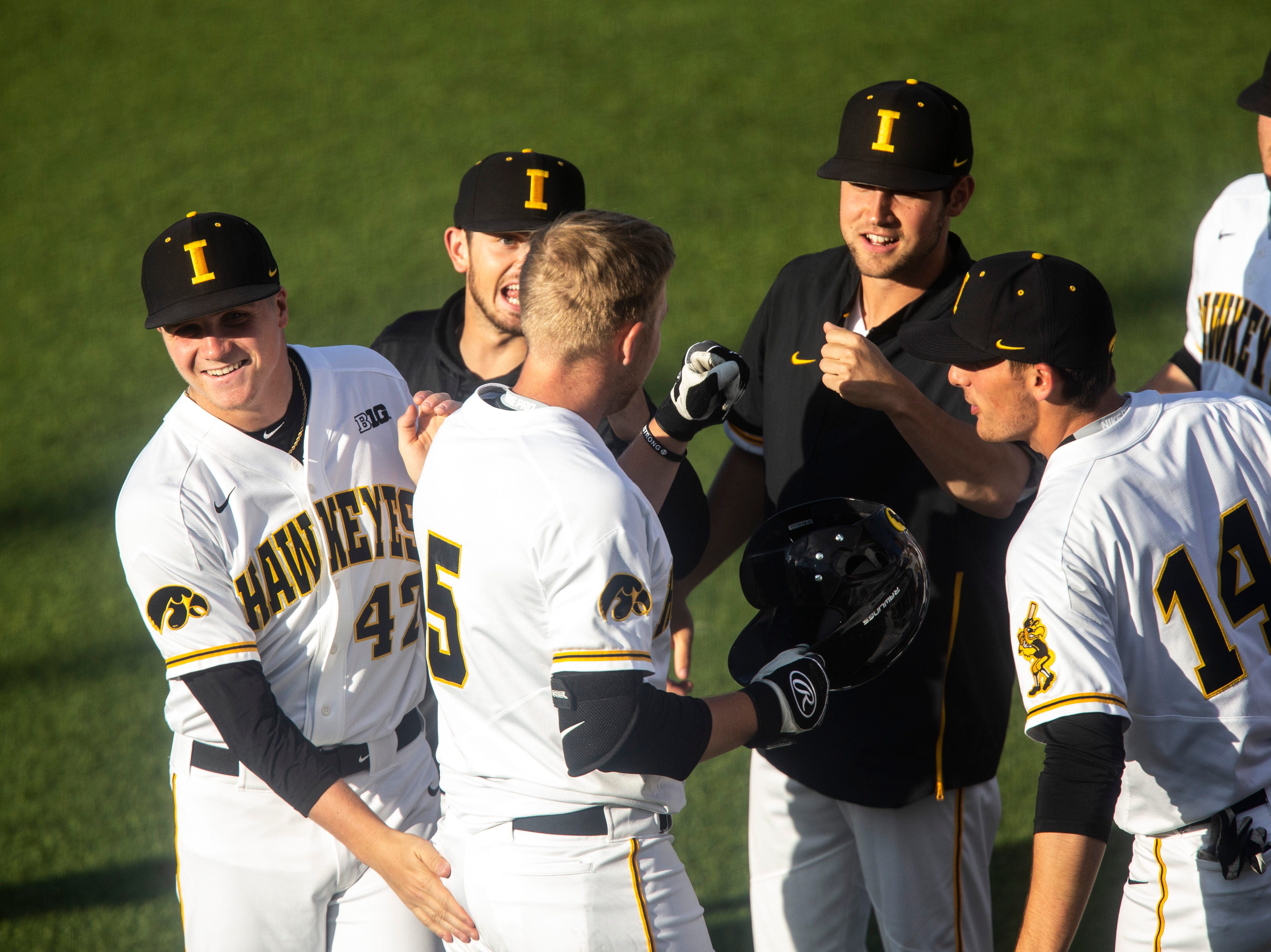 Iowa's Zeb Adreon (5) gets embraced by teammates after hitting a grand slam during a NCAA Big Ten Conference baseball game, Friday, May 10, 2019, at Duane Banks Field on the University of Iowa campus in Iowa City, Iowa.