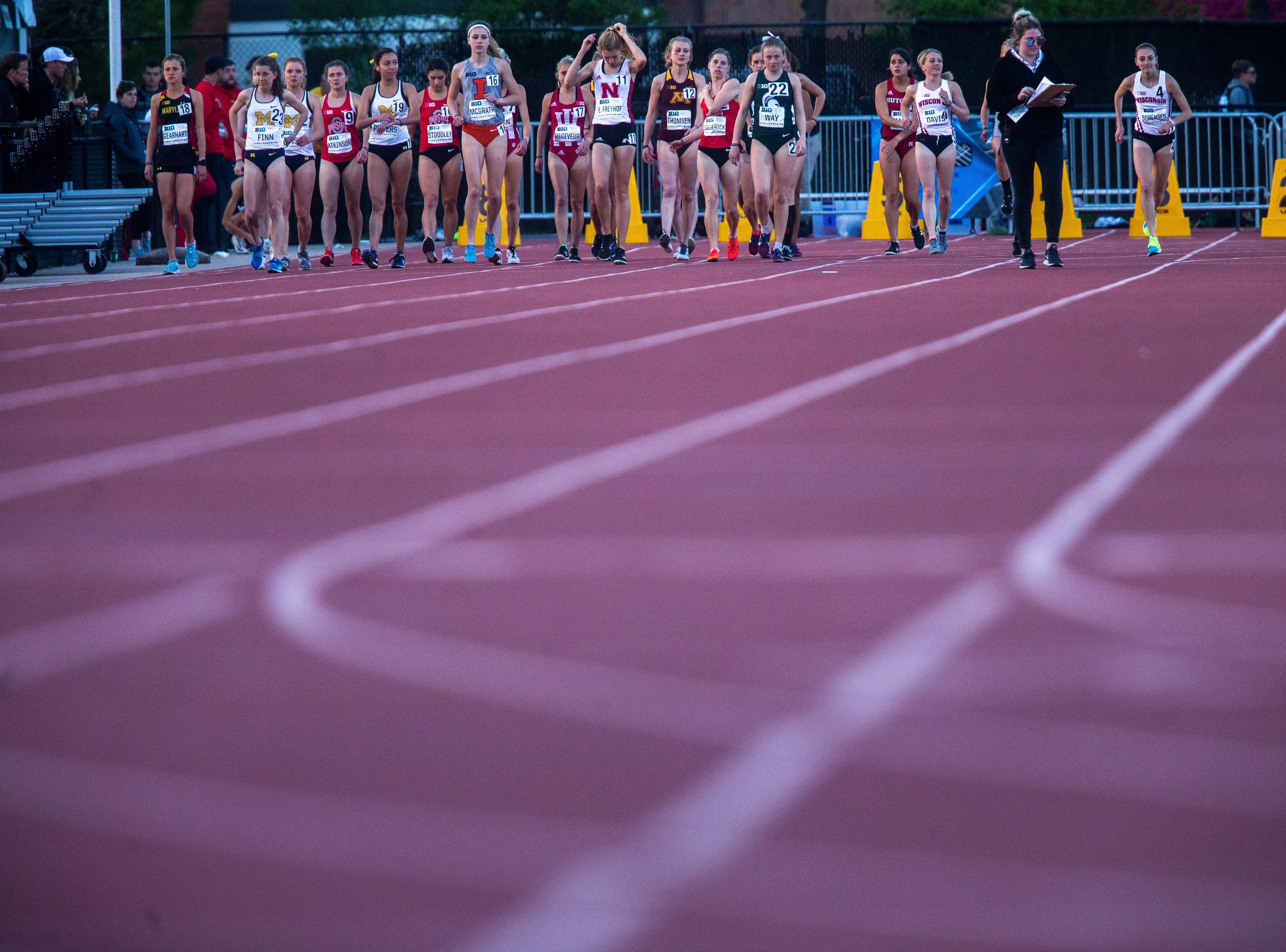 The field of women walk towards the start line before competing in the 10,000 meter during the first night of Big Ten track and field outdoor championships, Friday, May 10, 2019, at Francis X. Cretzmeyer Track on the University of Iowa campus in Iowa City, Iowa.