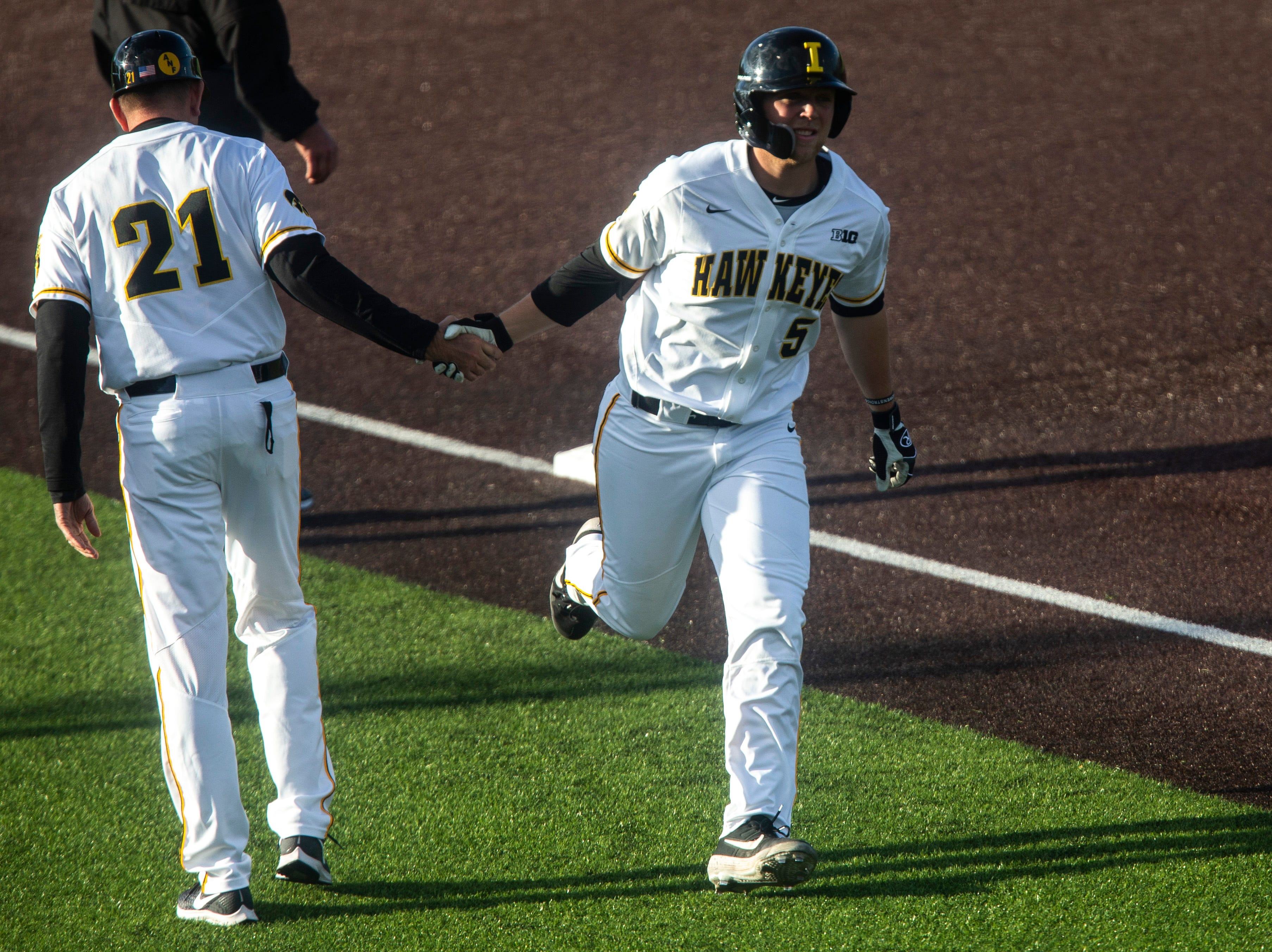 Iowa's Zeb Adreon (5) high-fives Iowa head coach Rick Heller while rounding third after hitting a grand slam during a NCAA Big Ten Conference baseball game, Friday, May 10, 2019, at Duane Banks Field on the University of Iowa campus in Iowa City, Iowa.