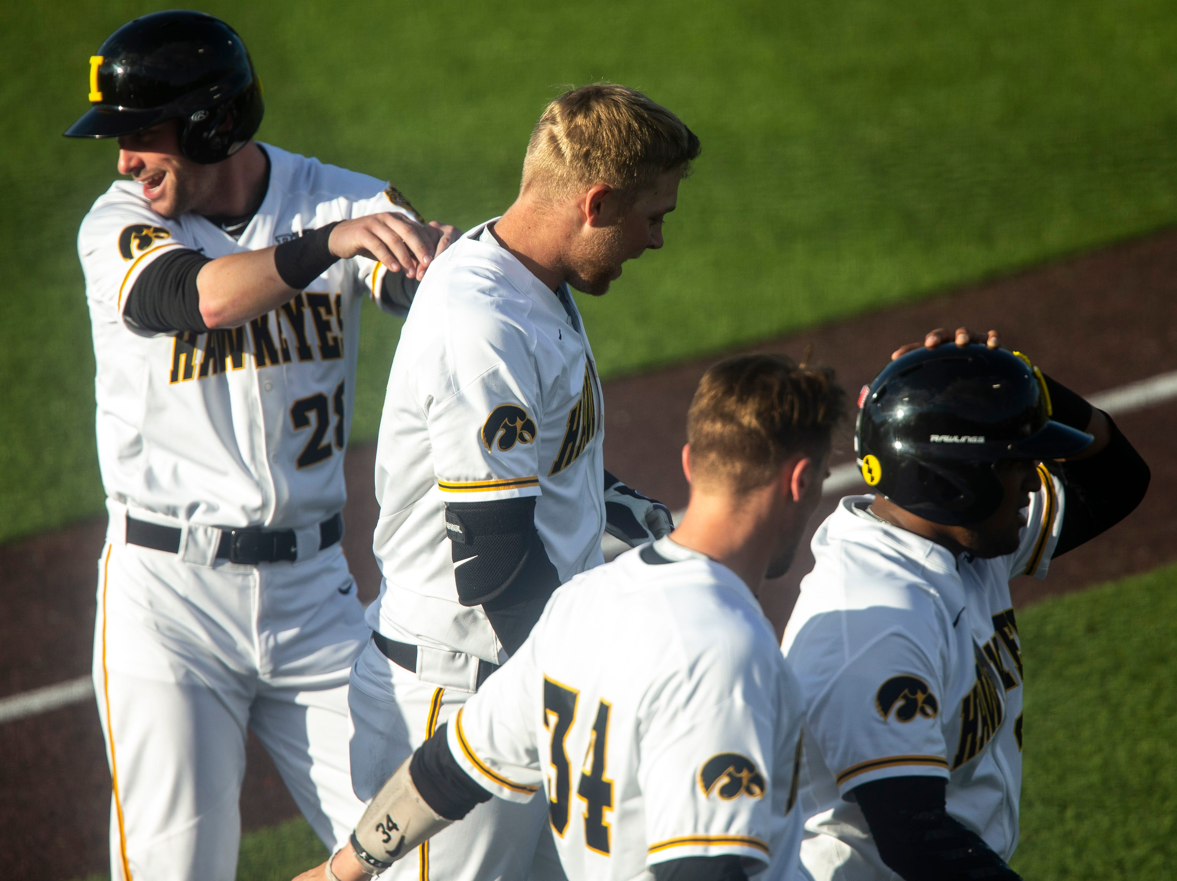 Iowa's Chris Whelan (28) gives teammate Zeb Adreon (5) a playful shove after Adreon hit a grand slam during a NCAA Big Ten Conference baseball game, Friday, May 10, 2019, at Duane Banks Field on the University of Iowa campus in Iowa City, Iowa.