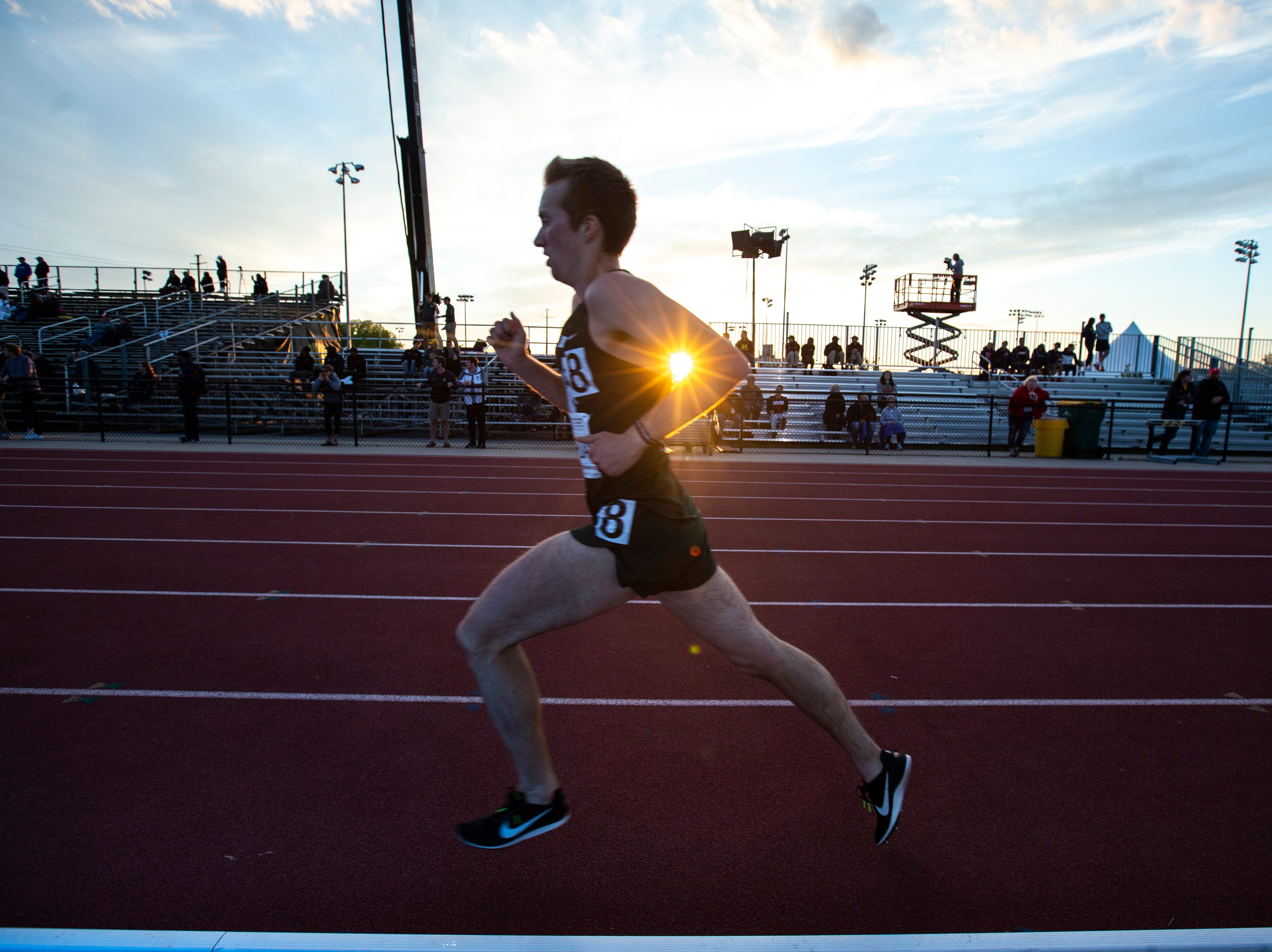 A burst of sun break through the arm of Michigan State sophomore Joe Riordan as he runs towards the front stretch while competing in the 10,000 meters during the first night of Big Ten track and field outdoor championships, Friday, May 10, 2019, at Francis X. Cretzmeyer Track on the University of Iowa campus in Iowa City, Iowa.