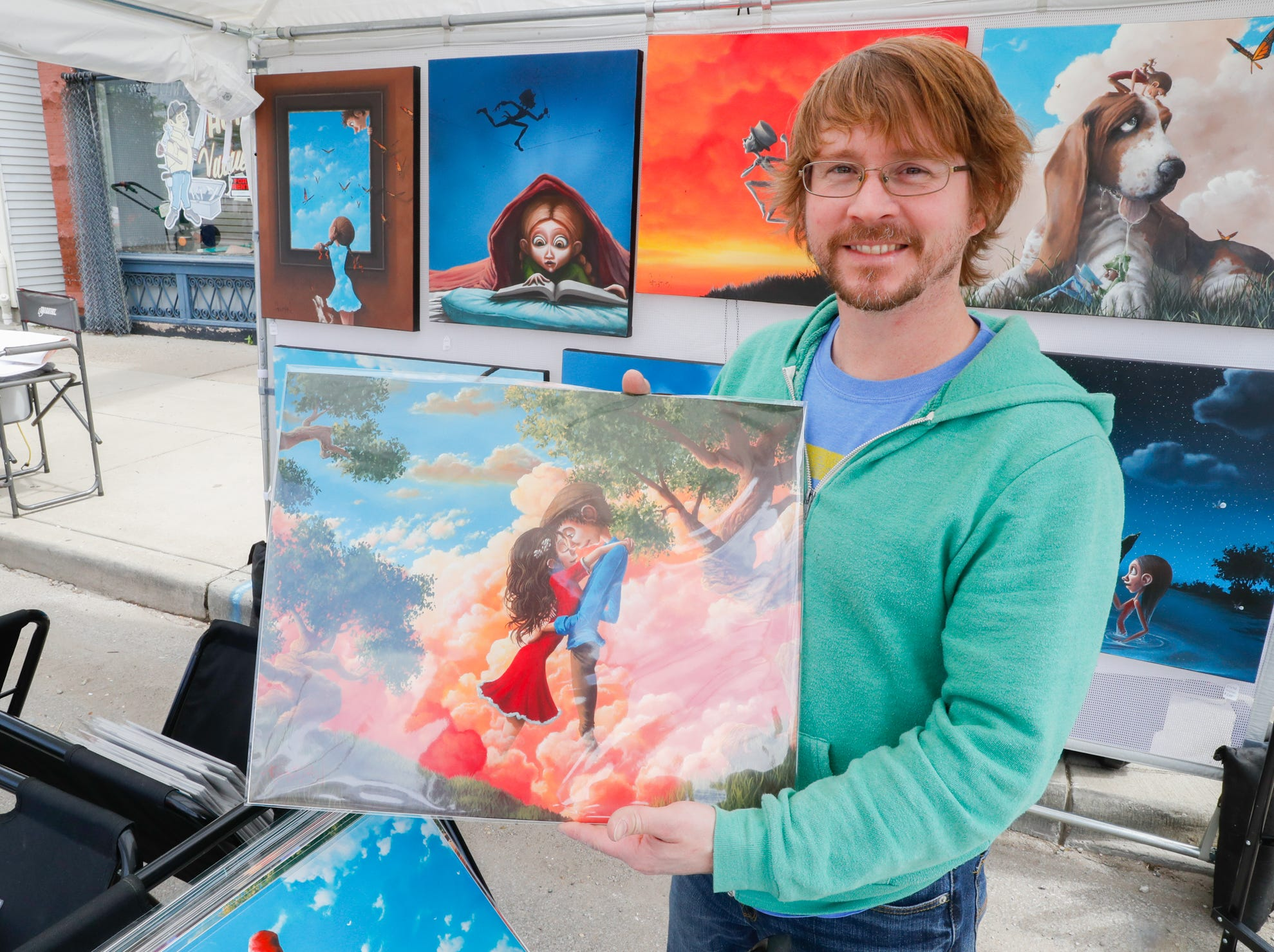 Artist Gabriel Lehman holds one of his prints up for sale at his booth, during the Virginia Avenue Music Fest, held in Fountain Square, located in Indianapolis, on Saturday, May 11, 2019.
