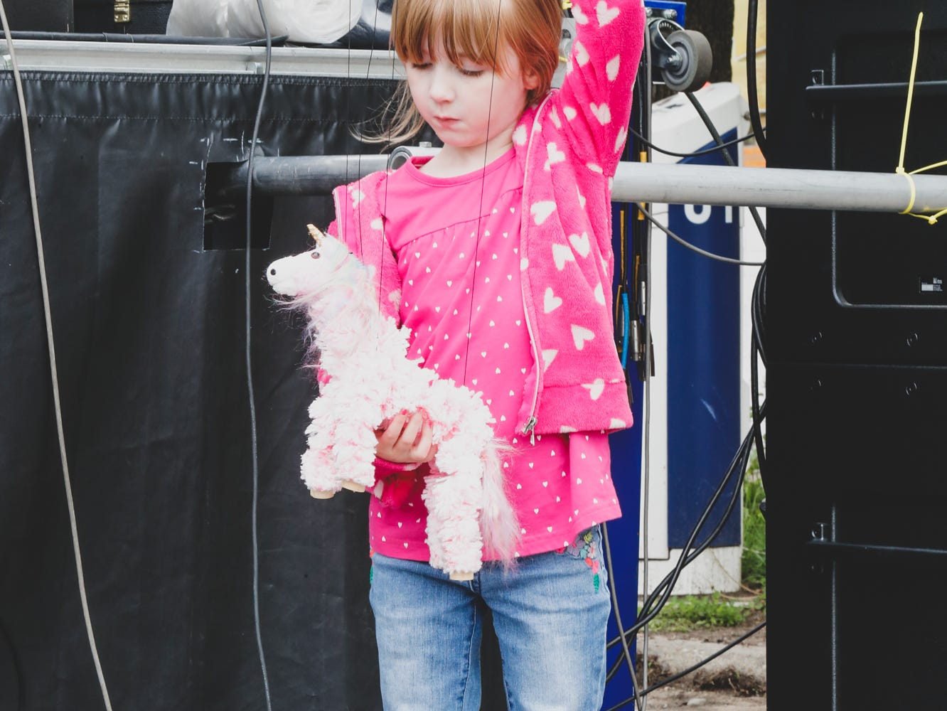 Gracelynn Schacke plays with her unicorn puppet while listening to Cairo Jag, during the Virginia Avenue Music Fest, held in Fountain Square, located in Indianapolis, on Saturday, May 11, 2019.