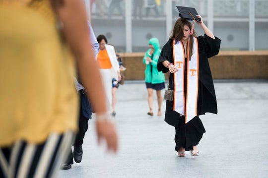 A student walks through the rain towards University of Tennessee's College of Arts and Sciences commencement in Thompson-Boling arena in Knoxville, Saturday, May 11, 2019.