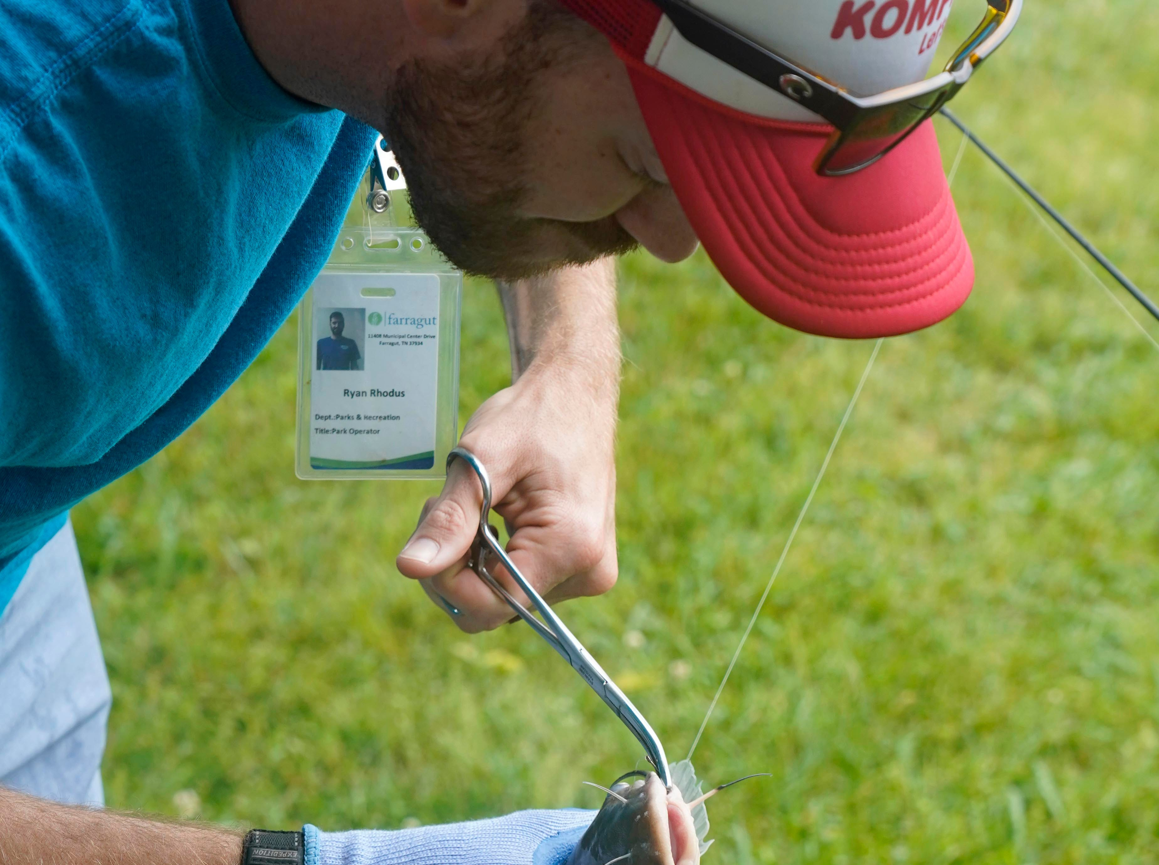 Ryan Rhodus, with the Town of Farragut, removes a hook  before weighing a fish during the 35th Annual Bob Watt Youth Fishing Rodeo was held Saturday, May. 11, 2019 at Anchor Park on Turkey Creek Road.
