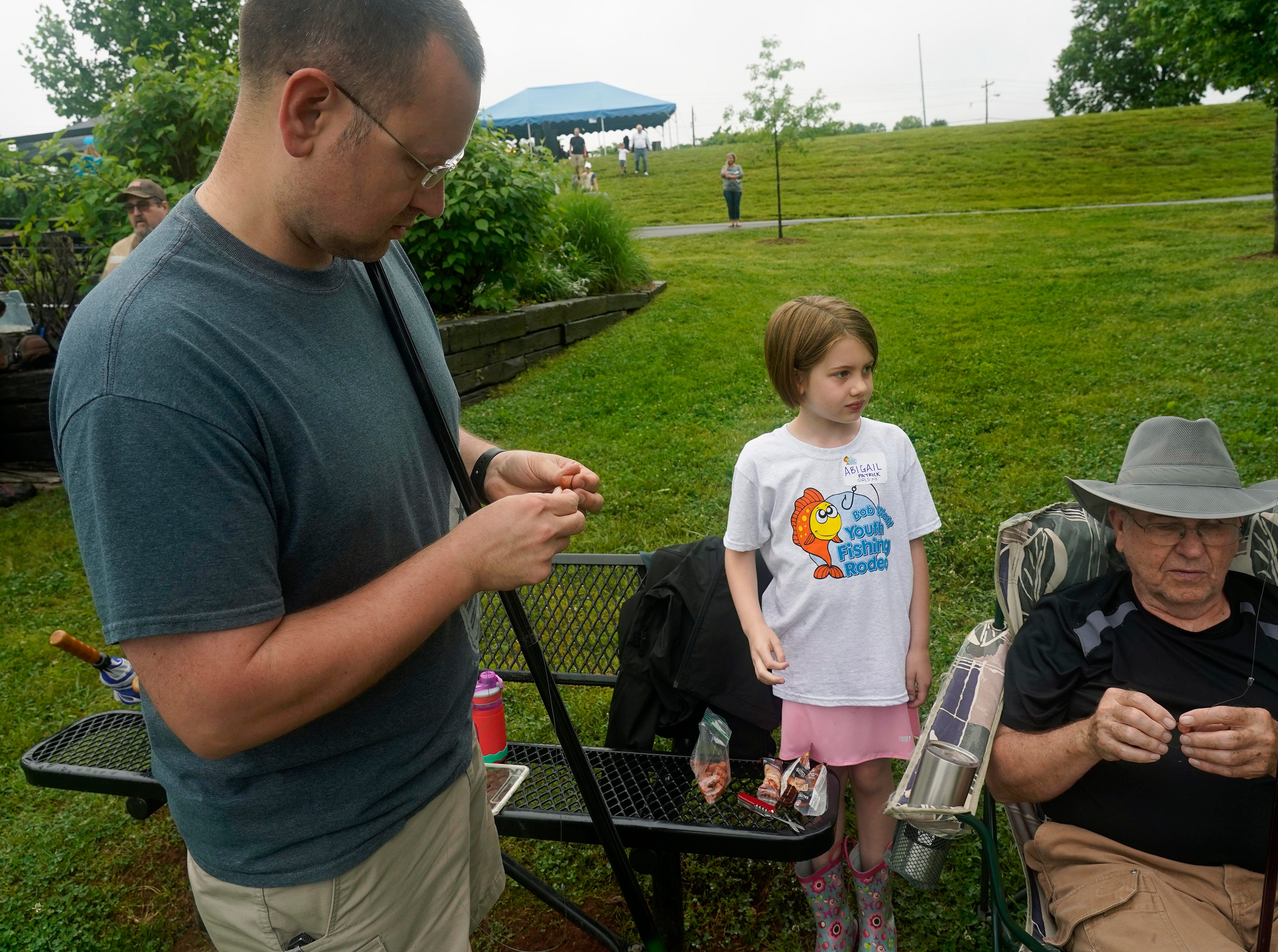 Ryan Patrick baits the hook for his daughter Abigail during the 35th Annual Bob Watt Youth Fishing Rodeo Saturday, May. 11, 2019 at Anchor Park on Turkey Creek Road.