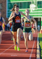 Brighton's Maddie Brown (486) passes Howell's Ashlyn Tait (744) just before the finish line to win the 800-meter run in the KLAA track and field meet on Friday, May 10, 2019.