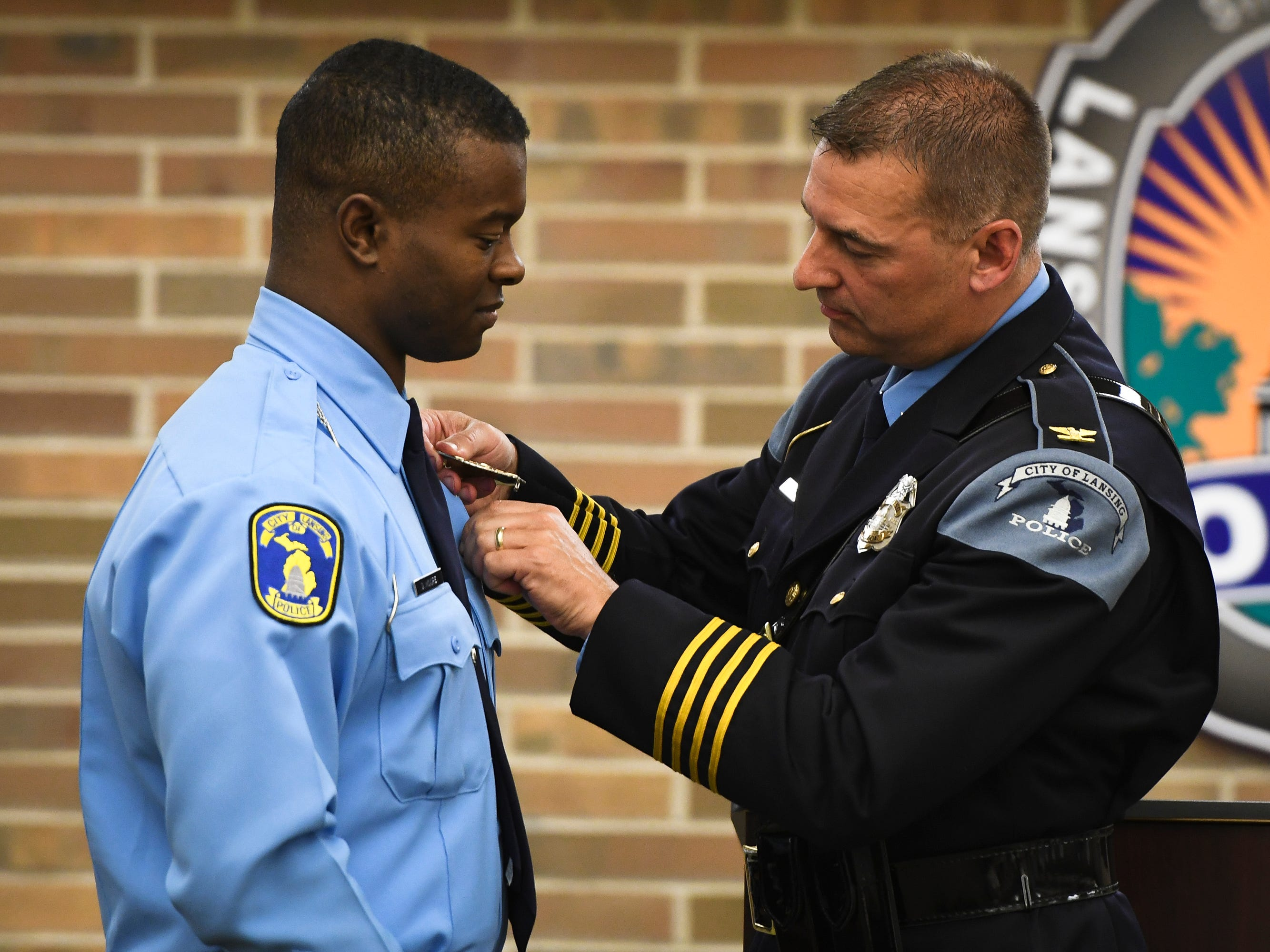 Chief Mike Yankowski, right, of the Lansing Police Department pins a badge on Donovan Moore, who was sworn in Monday, May 6, 2019, at the LPD Operations Center.