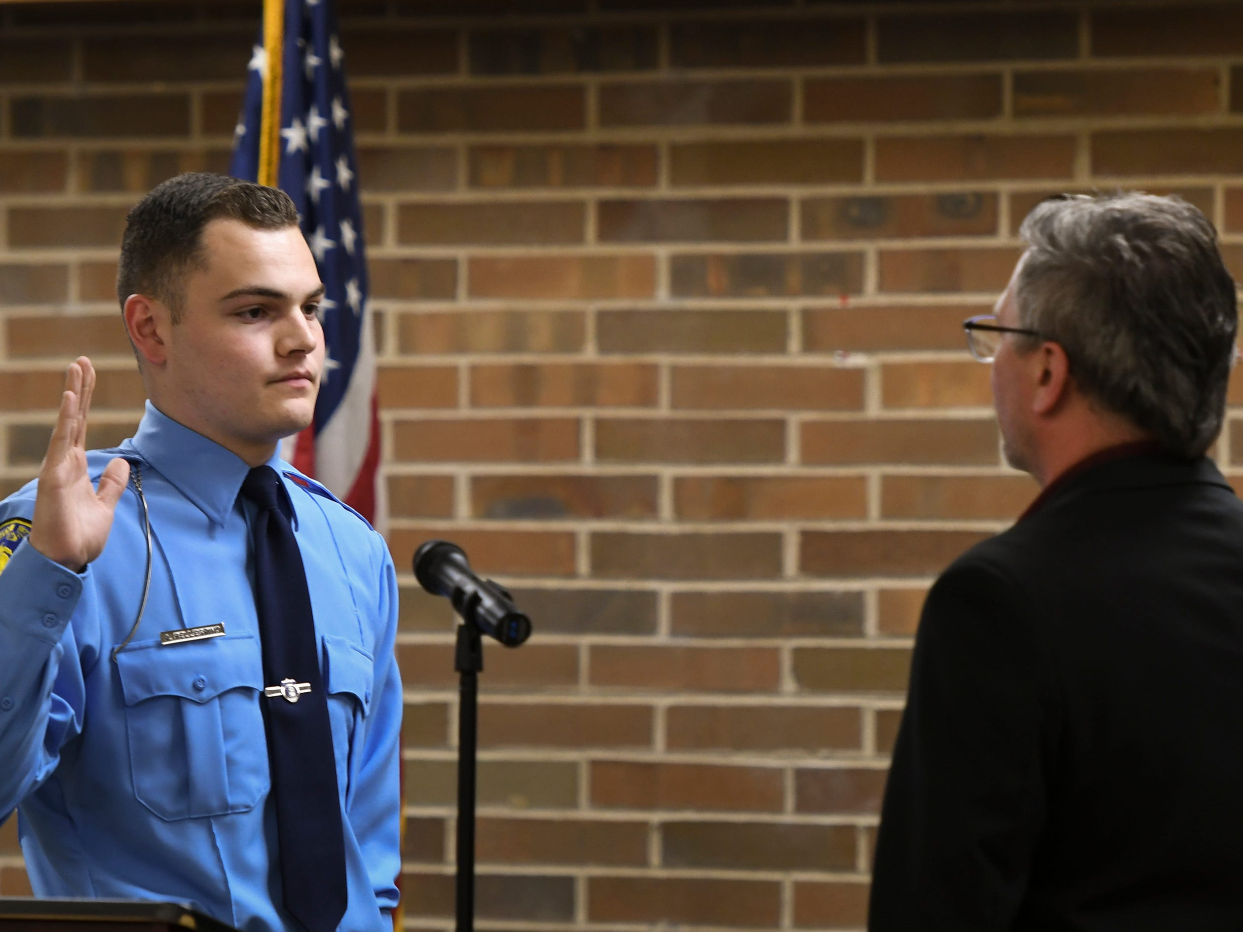 A.J. Pelligrino is sworn in by Lansing City Clerk Chris Swope, Monday, May 6, 2019, during the swearing in ceremony at the LPD Operations Center in Lansing.  Pelligrino served as an Explorer with LPD prior to the police academy.