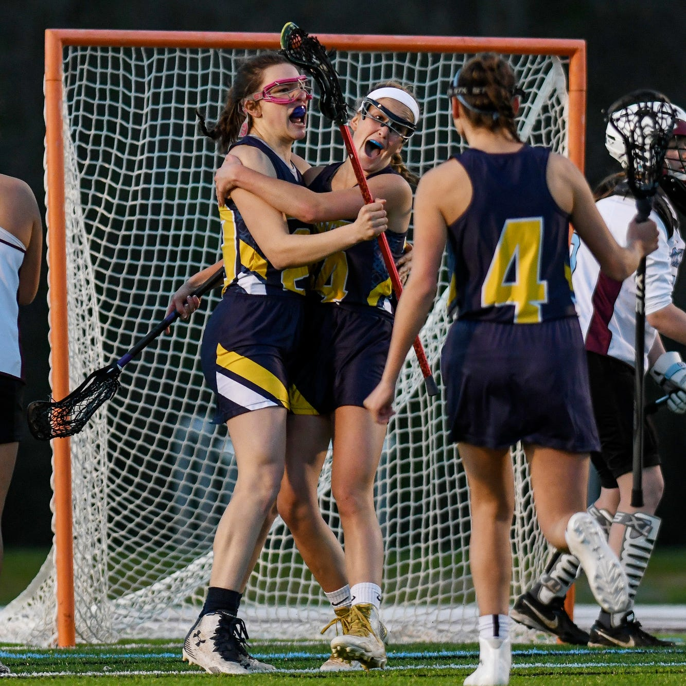DeWitt's Natalie Yabs, left, celebrates her game-winning goal with teammate Grace Brown during the second half on Friday, May 10, 2019, at Okemos High School. DeWitt beat Okemos 13-12 to win the CAAC tournament final.