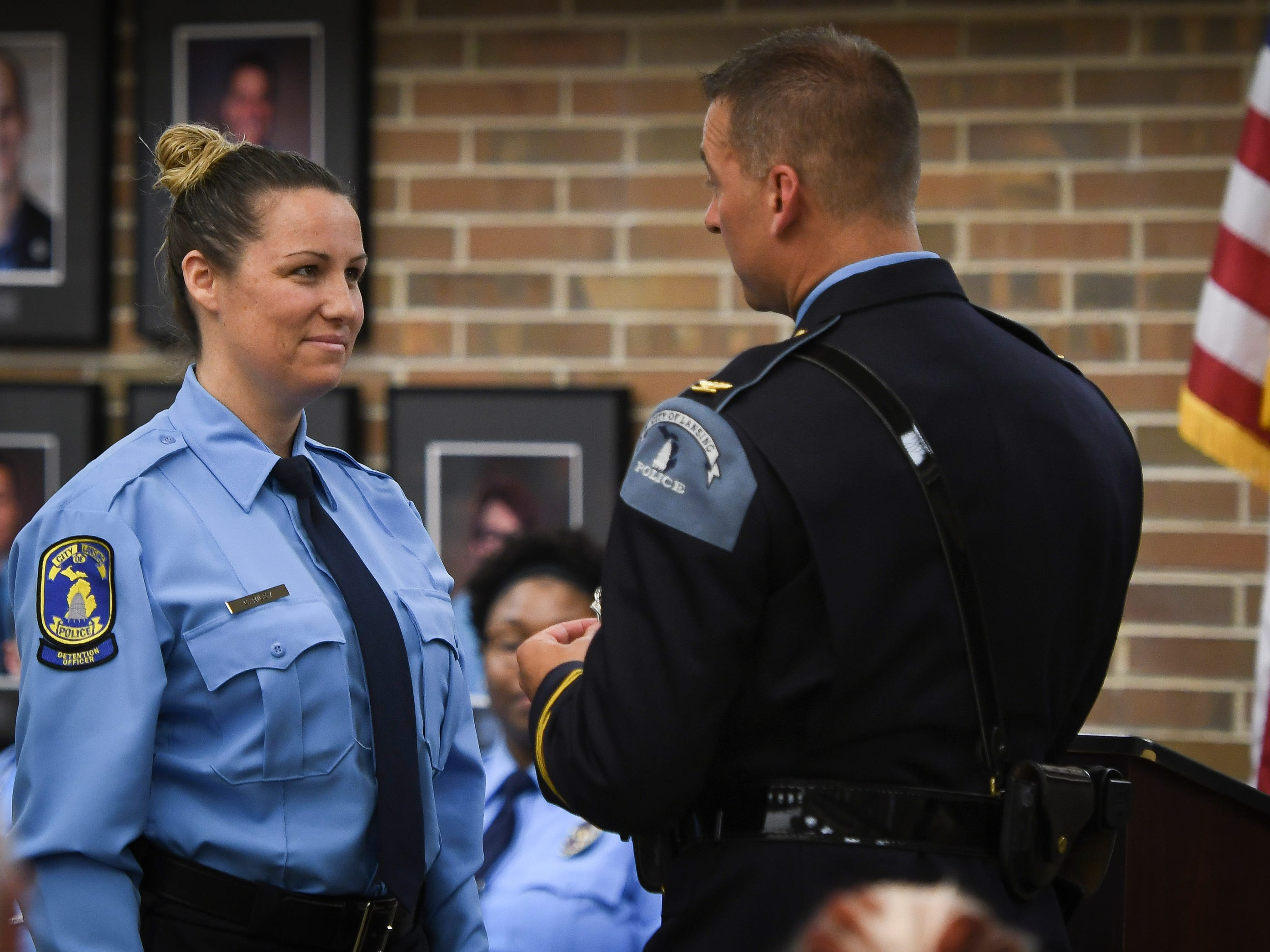 Chief Mike Yankowski of the Lansing Police Department prepares to pin a badge on newly sworn in detention officer Colleen Riley, Monday, May 6, 2019, during the swearing in ceremony at the Lansing Police Operations Center.
