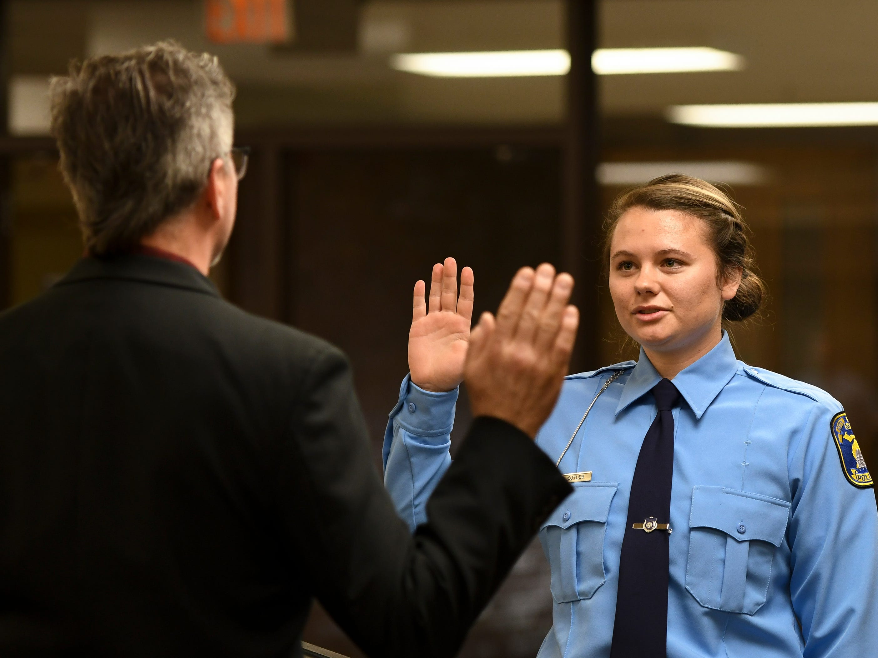 Ali Cutler is sworn in by Lansing City Clerk Chris Swope, Monday, May 6, 2019, during the swearing in ceremony at the LPD Operations Center in Lansing.