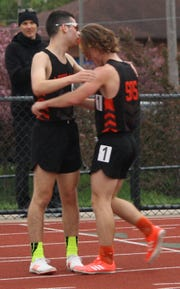 Ashland's Reid McFrederick and Cohan Robinson celebrate finishing 1-2, respectively, in the 3200, which all but sewed up a fourth straight Ohio Cardinal Conference title for the Arrows.