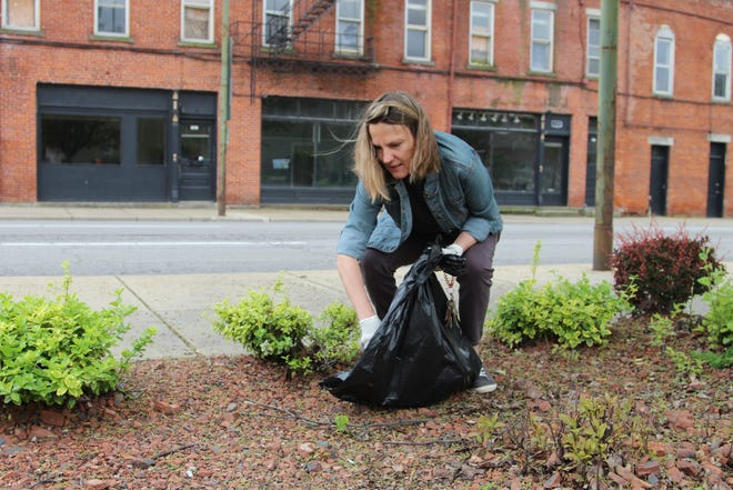 Cheri White picks up trash and cigarette butts Friday at Founders Park in downtown Marion, at the corners of Main and Church streets, during the 2019 Earth Day clean-up of downtown. It was White's first time participating in the yearly clean-up event.