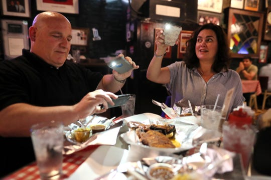 Food writers Brad Schmitt of The Tennessean and Jennifer Chandler of The Commercial Appeal photograph their food at Rendezvous during a tour of Memphis barbecue joints Friday, May 10, 2019.
