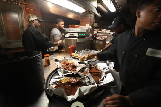 Kitchen workers prepare a tray of meats at Rendezvous on Friday, May 10, 2019.