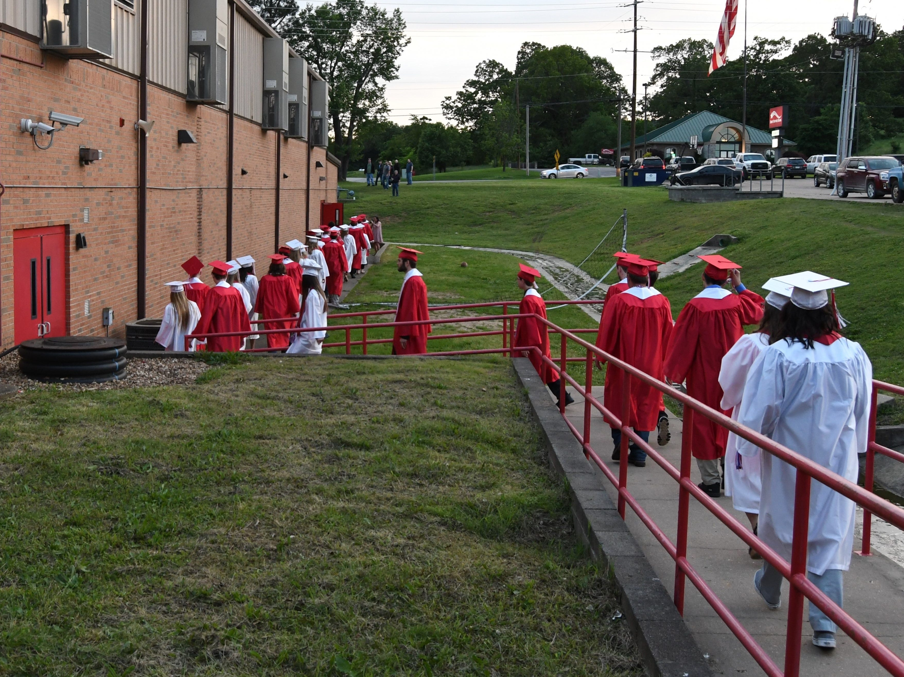 Flippin seniors walk from one end of the school's gymnasium to the other to begin Friday night's graduation ceremony.