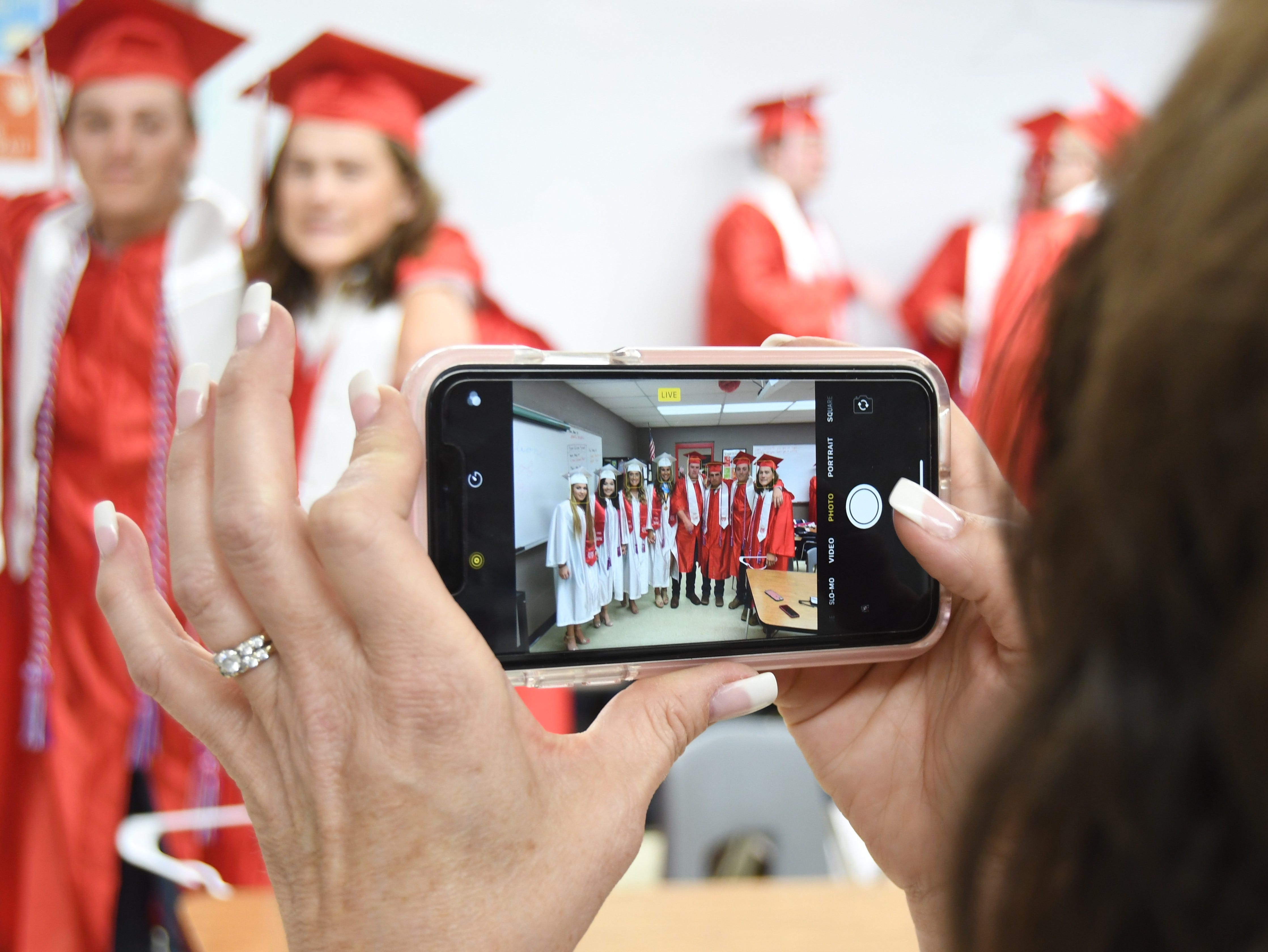 Senior class sponsor Gina Riggs snaps a photo of a group of Flippin seniors Friday night before they graduate.