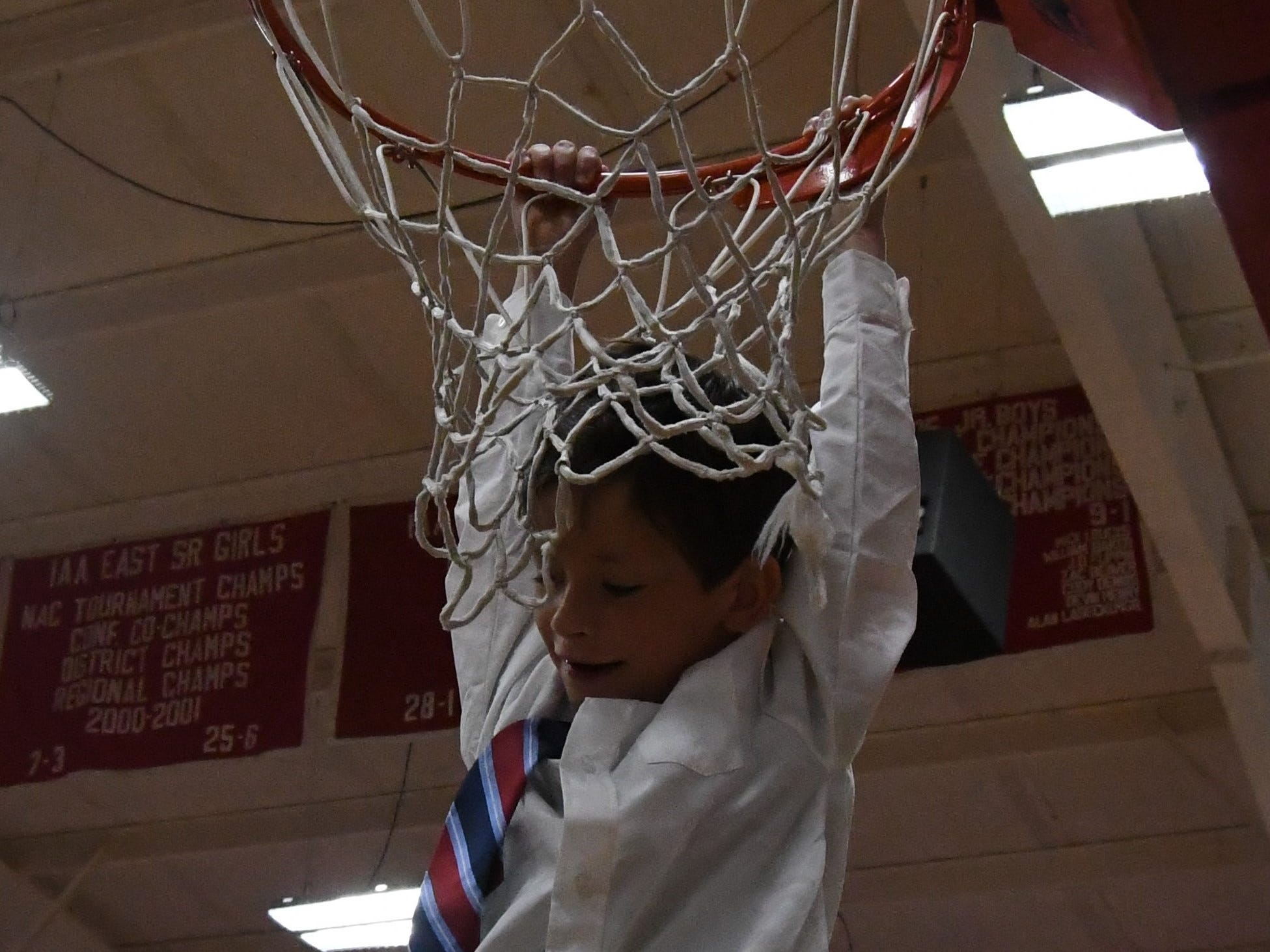 A Flippin graduation attendee gets a helping hand to hang on the gym's basketball rim following Friday night's graduation.