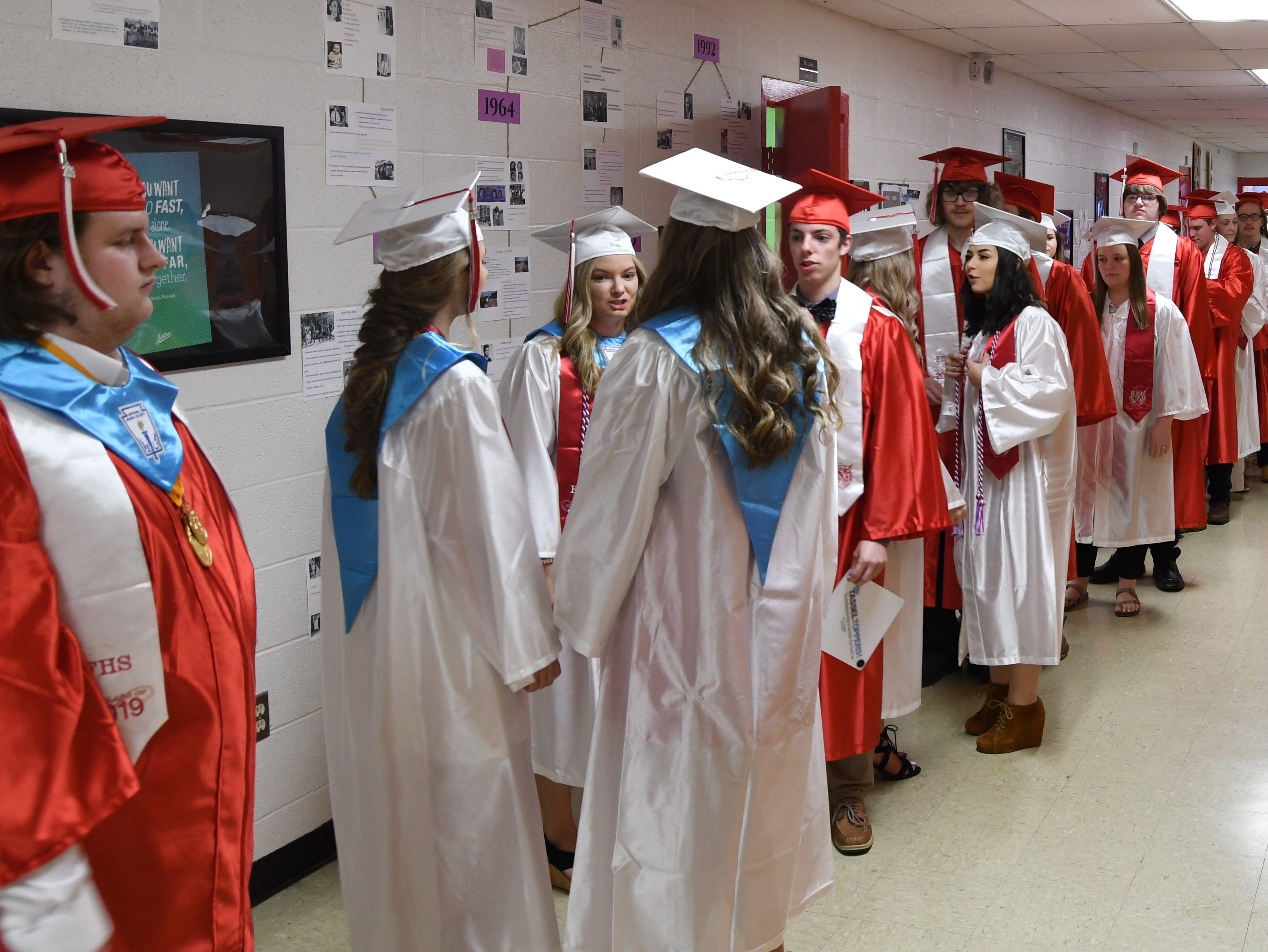 Flippin seniors line up in the hallway before graduation ceremonies start Friday night.