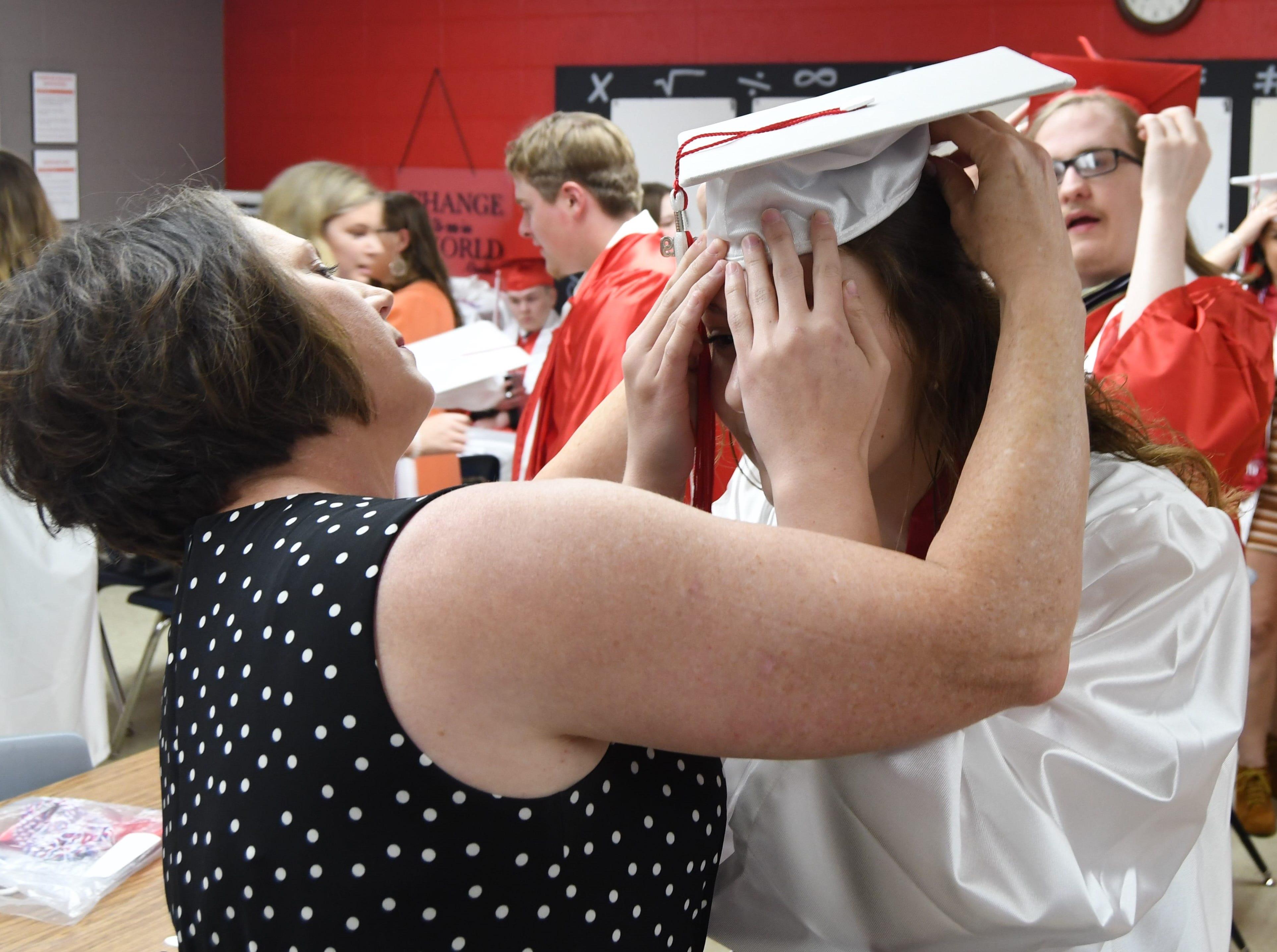 Senior class sponsor Gina Riggs helps a Flippin senior adjust her cap before Friday night's graduation.