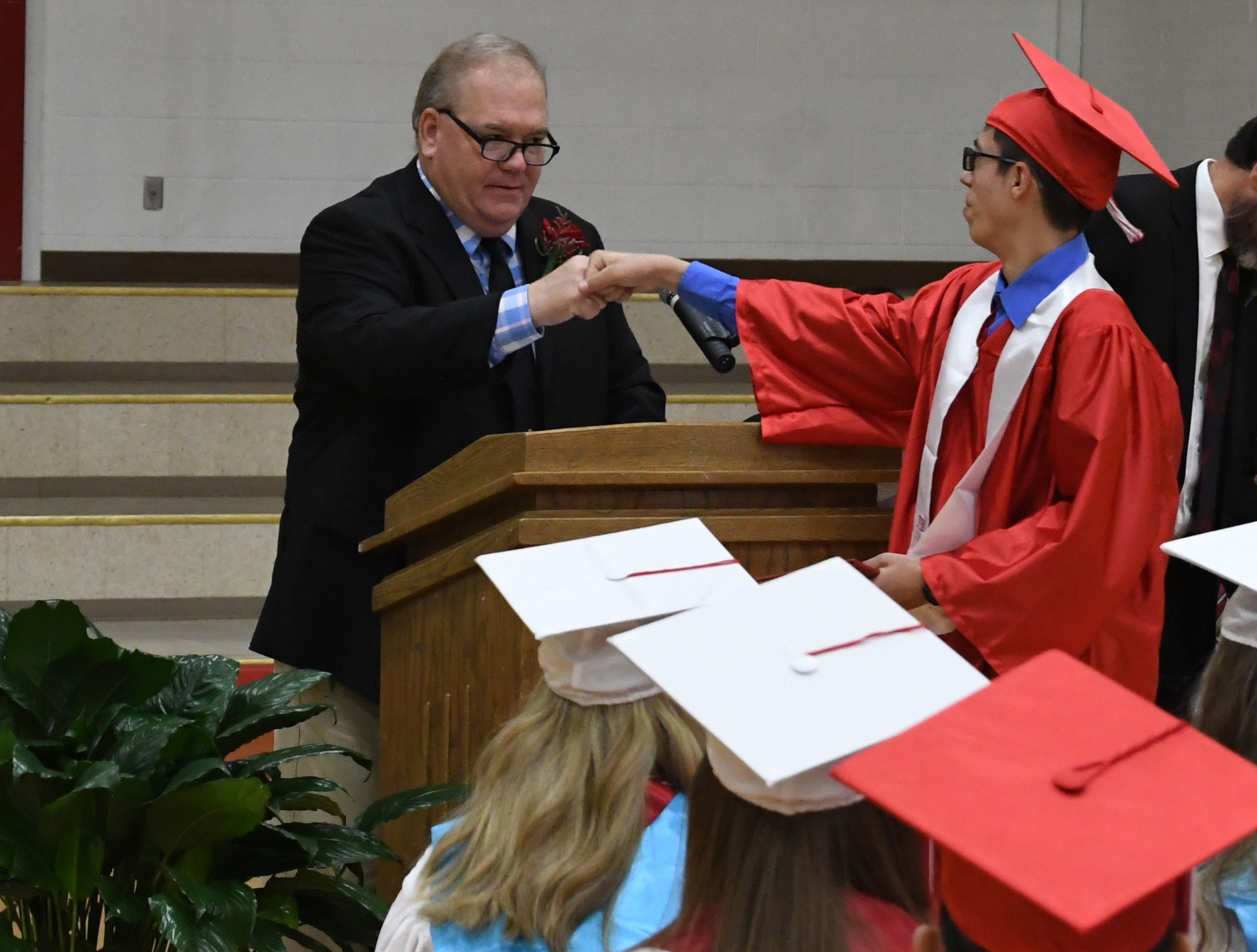A Flippin graduate bumps fists with high school principal Dale Horn after receiving his diploma on Friday night in Flippin.