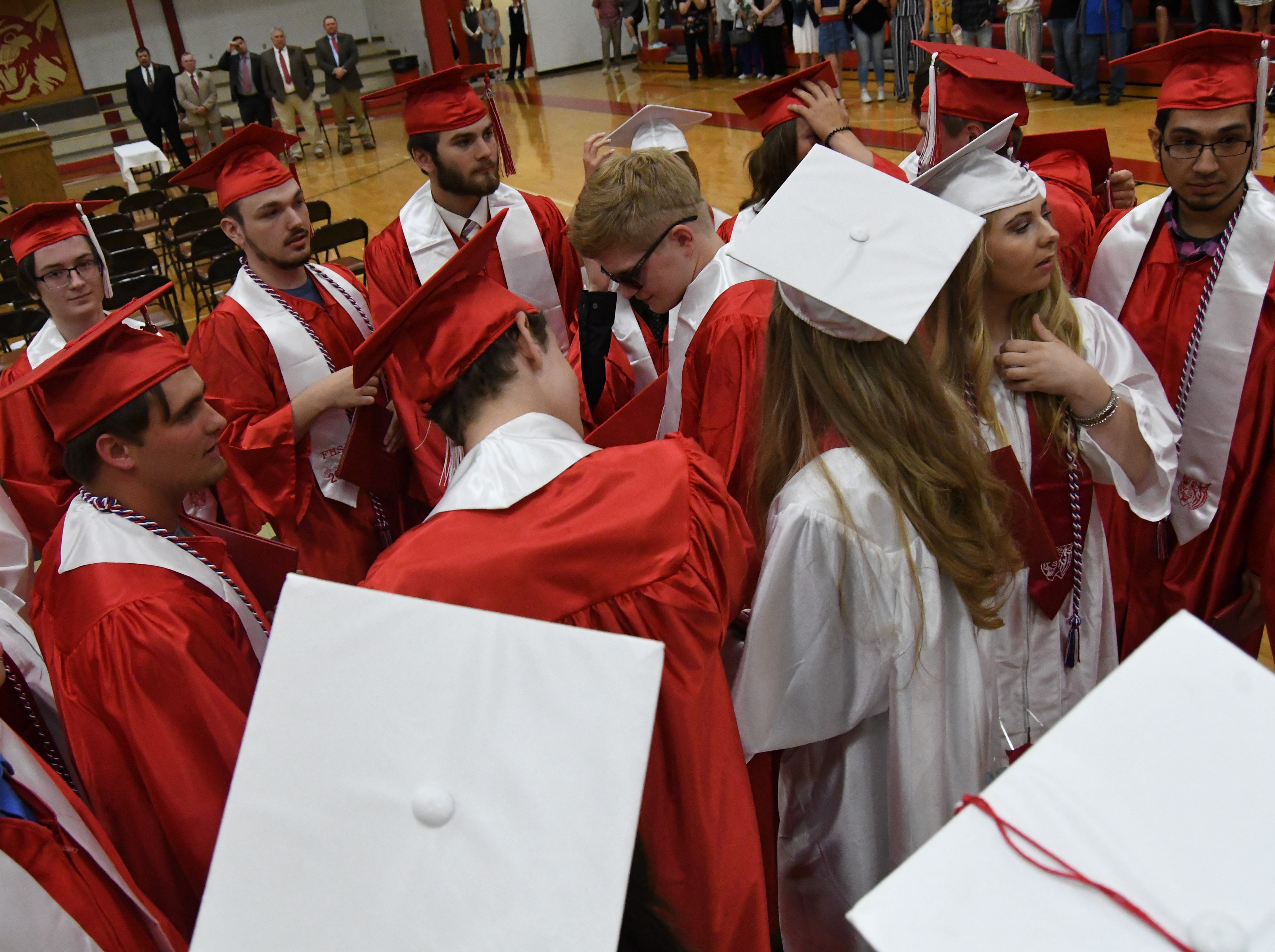 Flippin graduates gather on the gym floor before throwing their caps into the air Friday night.