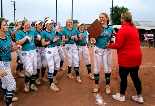 Siegel's Caitlyn McCrary (10) accepts the 7-AAA District softball Championship trophy after beating Blackman in the Championship game at Oakland on Friday, May 10, 2019.