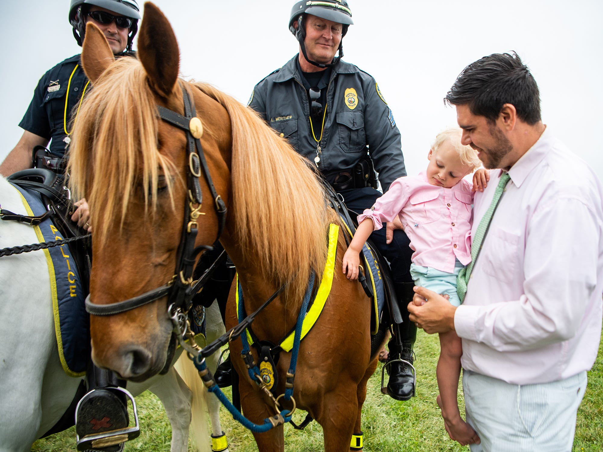 Brian Kelly holds his son Henry Knestrick, 3, to pet a police horse during the Iroquois Steeplechase at Percy Warner Park Saturday, May 11, 2019, in Nashville, Tenn.