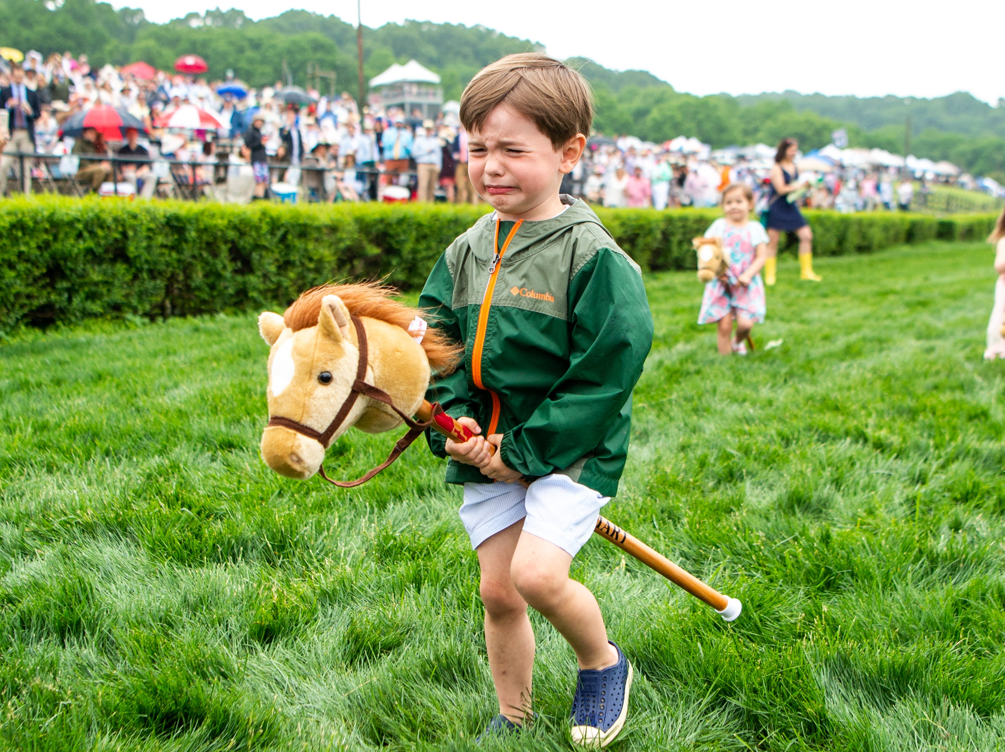 A child cries while competing in the stick horse race during the Iroquois Steeplechase at Percy Warner Park Saturday, May 11, 2019, in Nashville, Tenn.