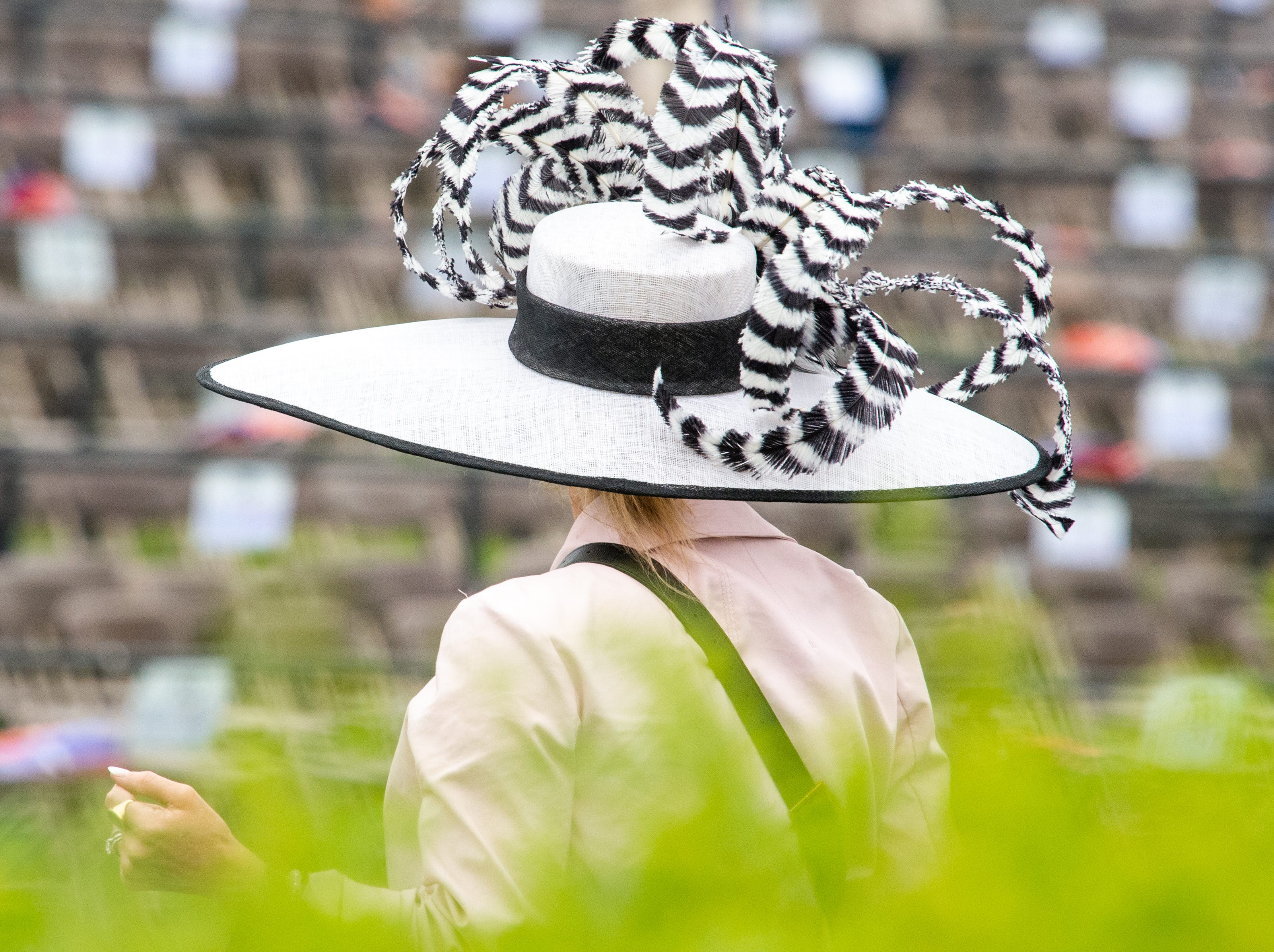 A fan walks across the track in a large hat during the Iroquois Steeplechase at Percy Warner Park Saturday, May 11, 2019, in Nashville, Tenn.