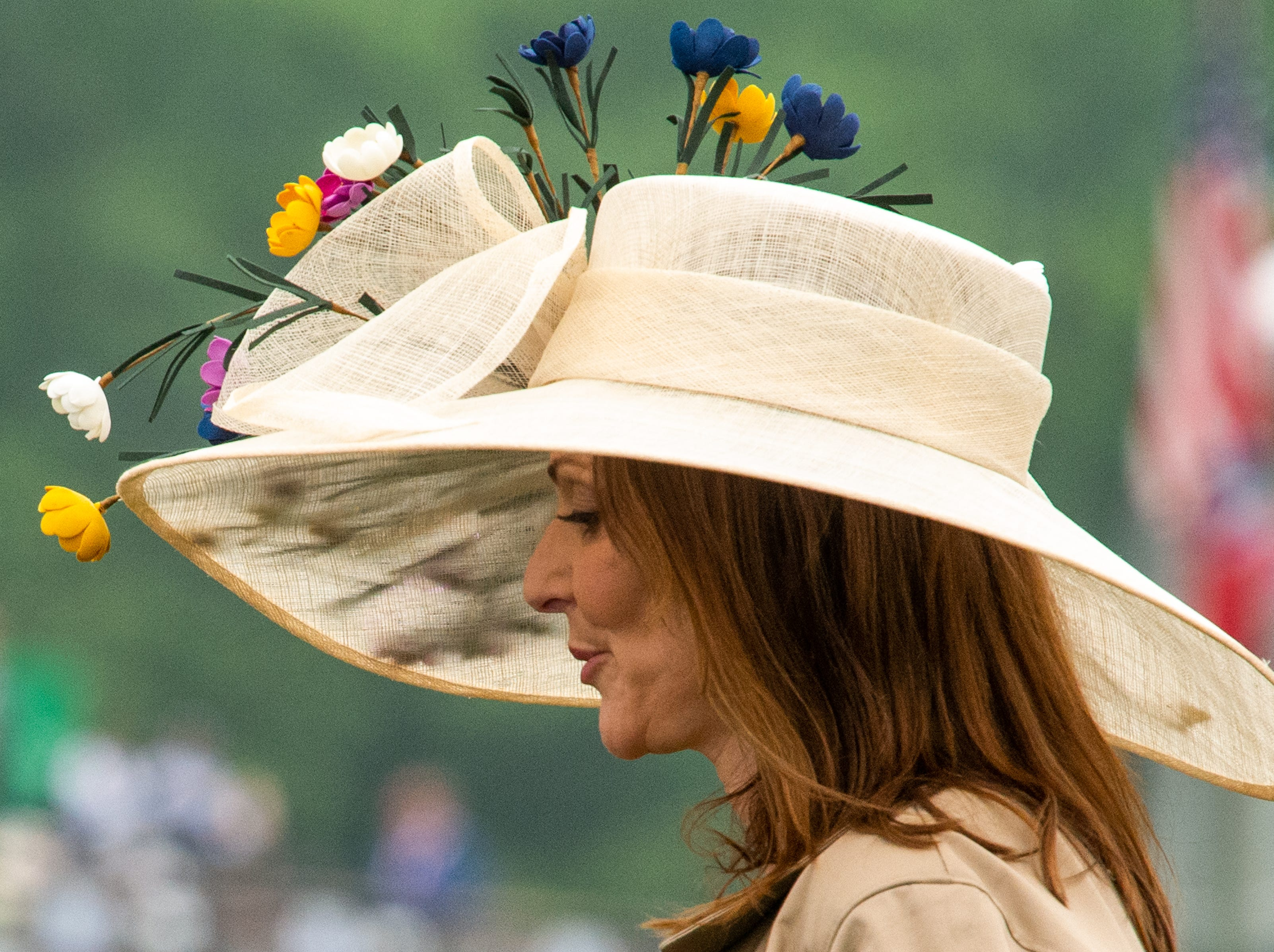A fan walks with a floral hat during the Iroquois Steeplechase at Percy Warner Park Saturday, May 11, 2019, in Nashville, Tenn.