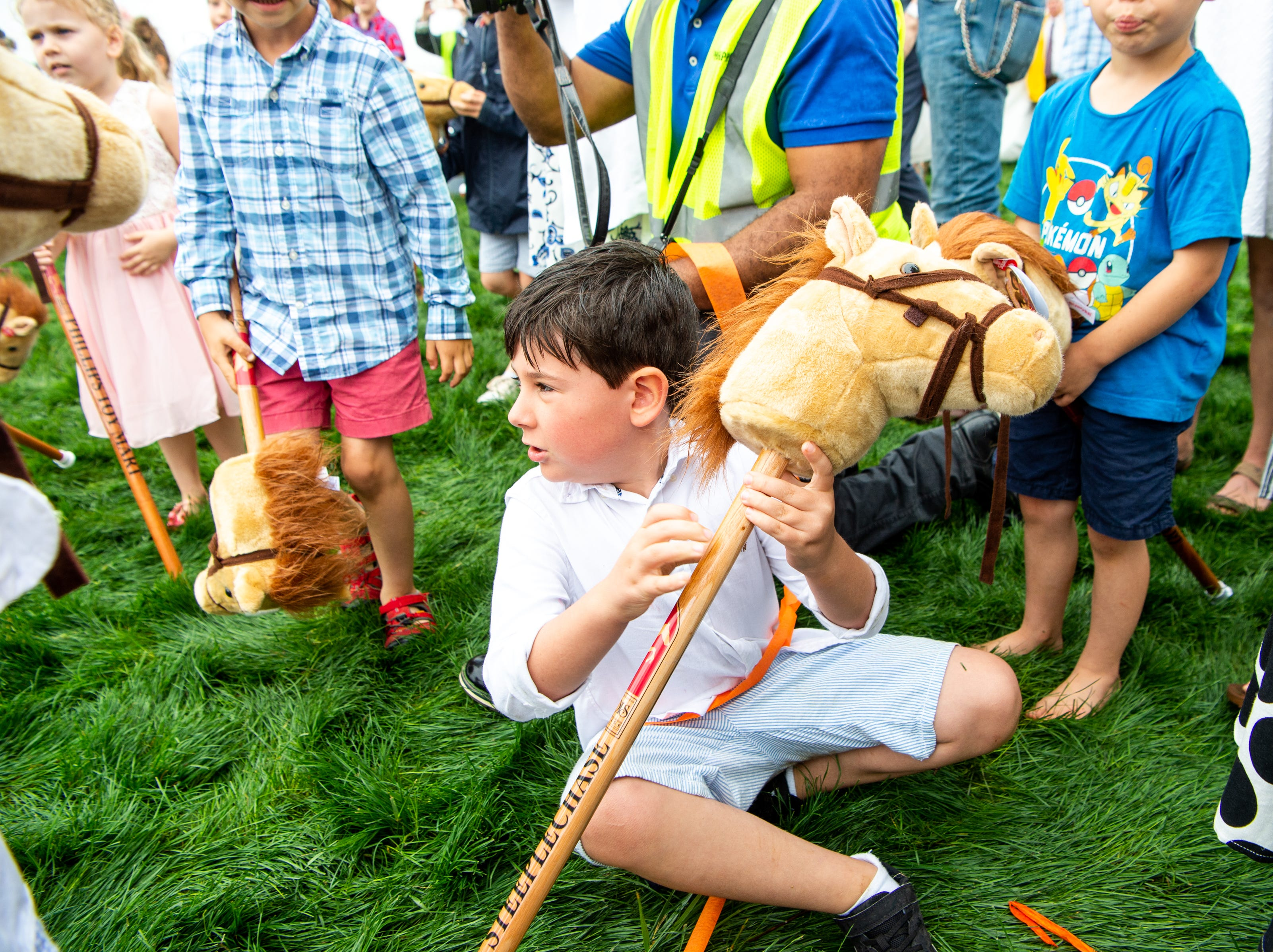 A child sits after competing in the stick horse race during the Iroquois Steeplechase at Percy Warner Park Saturday, May 11, 2019, in Nashville, Tenn.