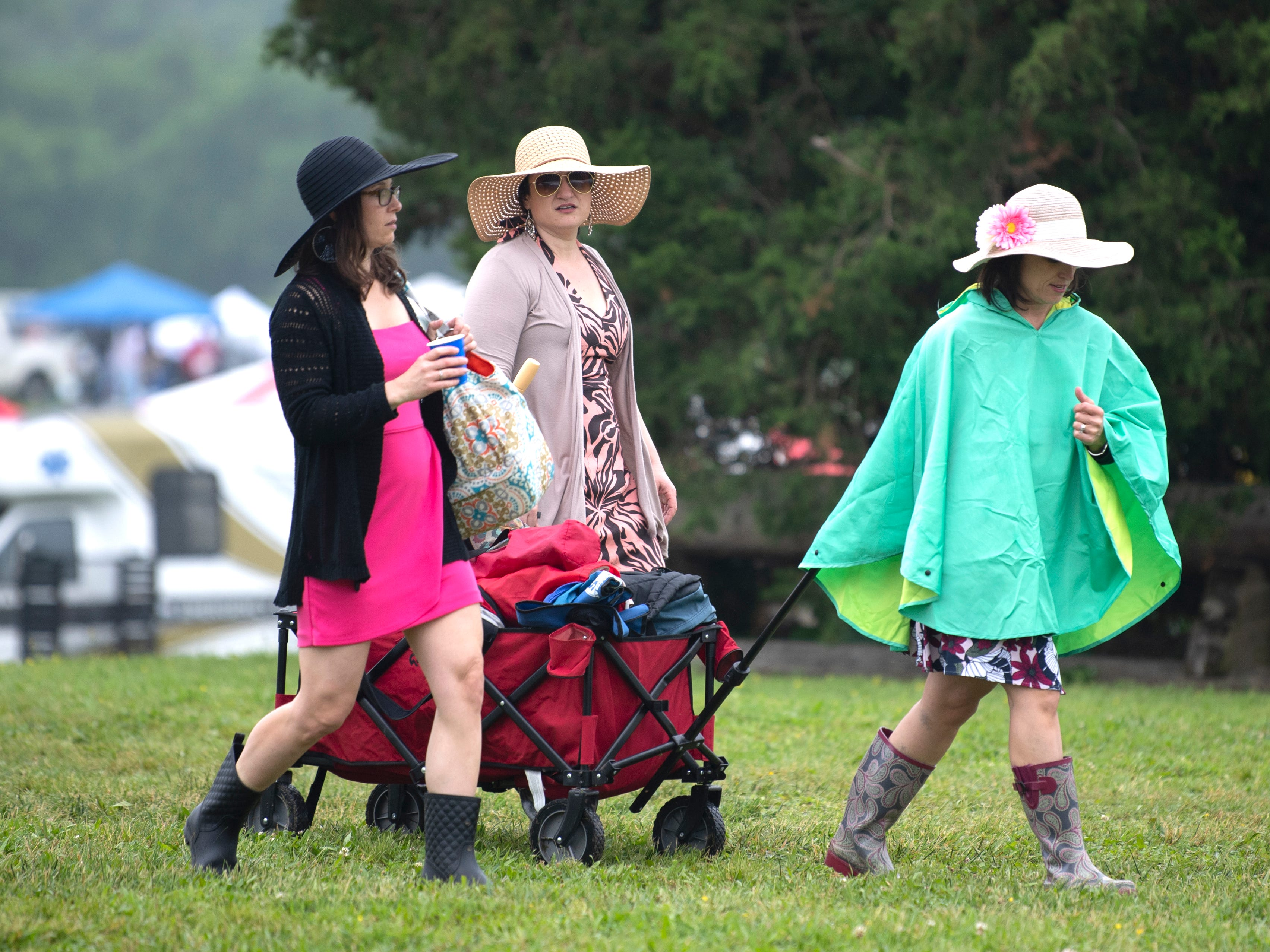 Horse racing fans carry belongings for tailgating at the 78th Iroquois Steeplechase at Percy Warner park in Nashville on Saturday, May, 11, 2019.