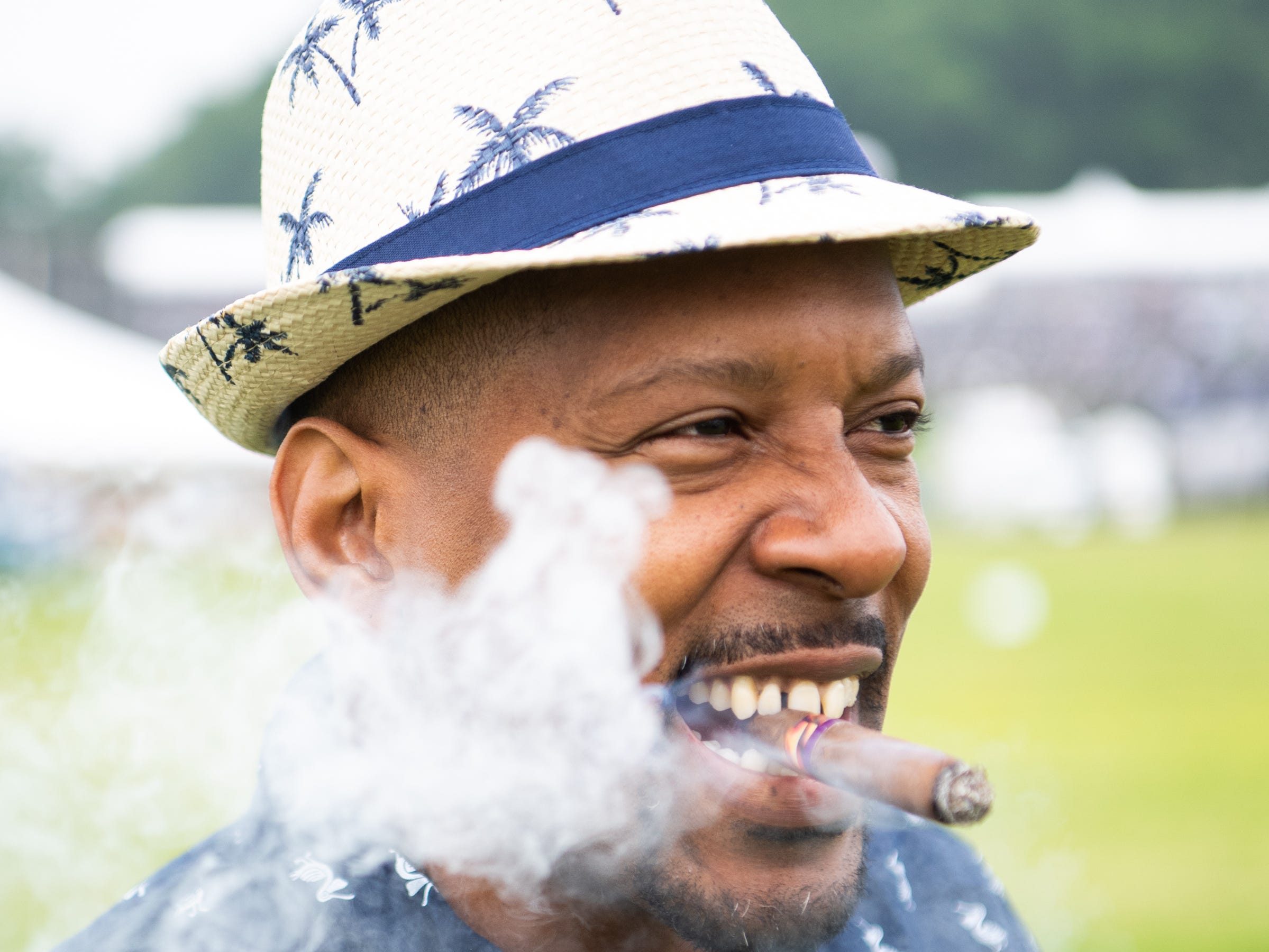 Jonte Mayor Gaines smokes a cigar during the Iroquois Steeplechase at Percy Warner Park Saturday, May 11, 2019, in Nashville, Tenn.
