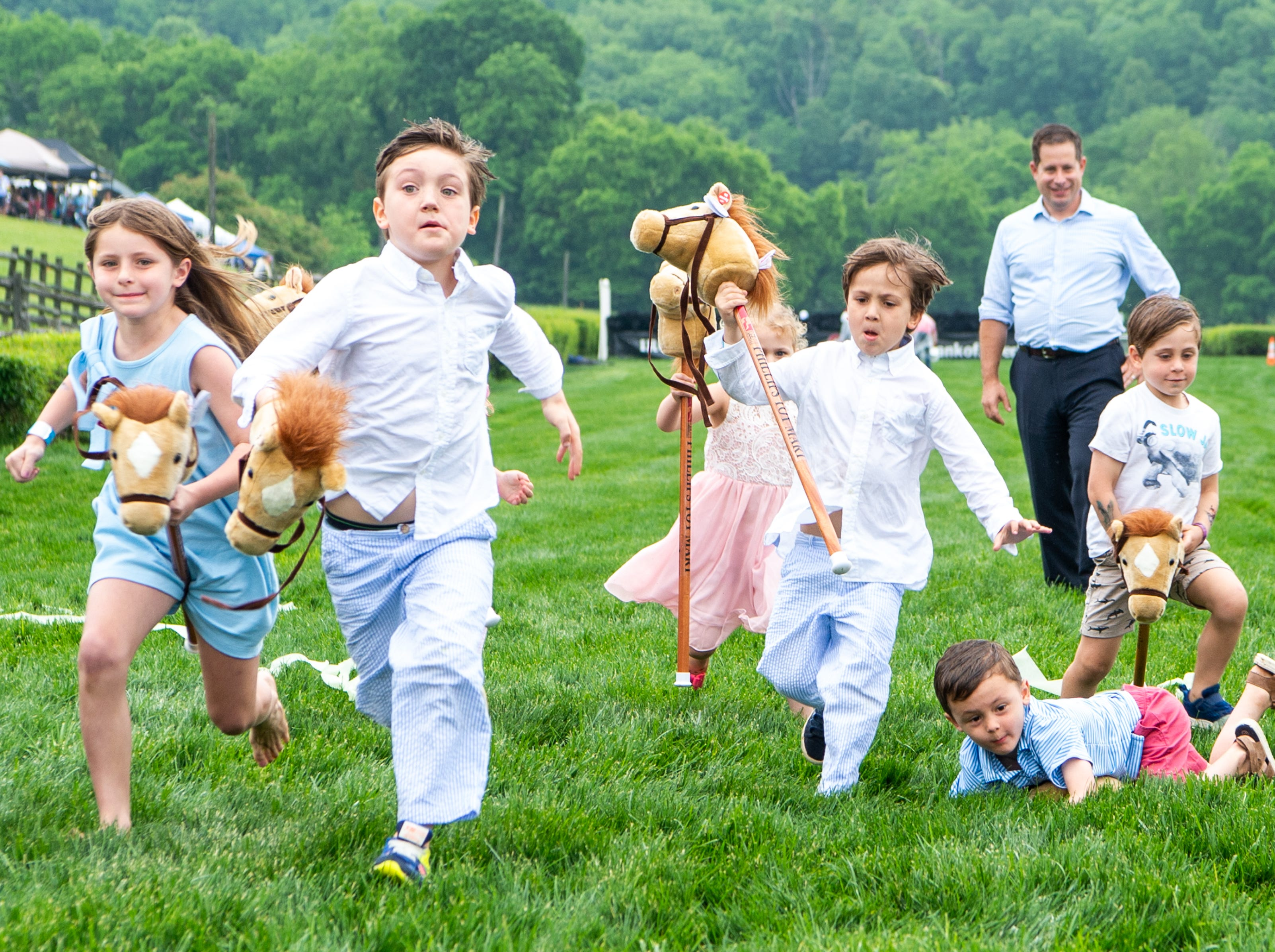 Children compete in the stick horse race during the Iroquois Steeplechase at Percy Warner Park Saturday, May 11, 2019, in Nashville, Tenn.