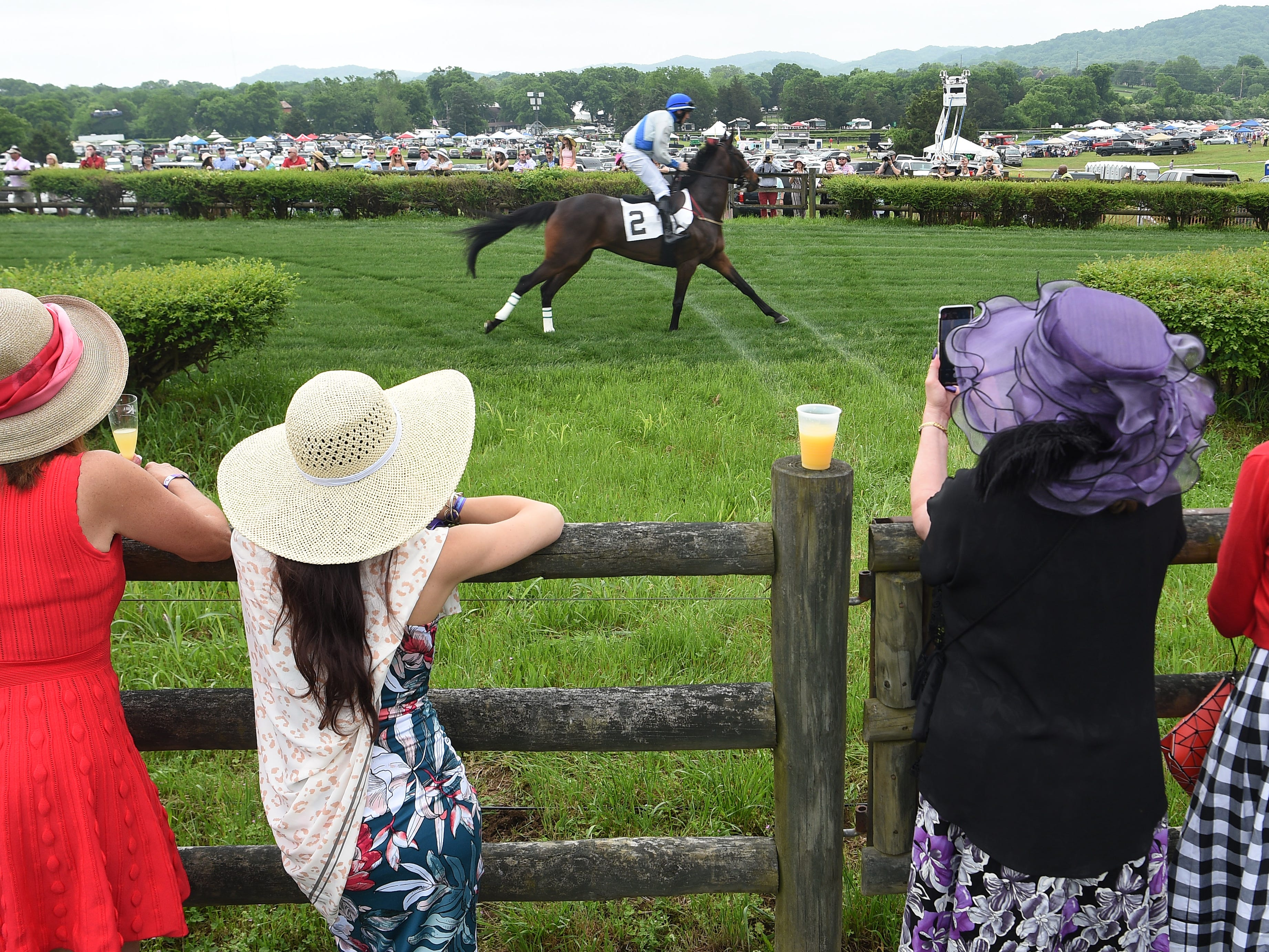 Spectators watch horses warm up for the 78th Iroquois Steeplechase at Percy Warner Park in Nashville on Saturday, May 11, 2019.
