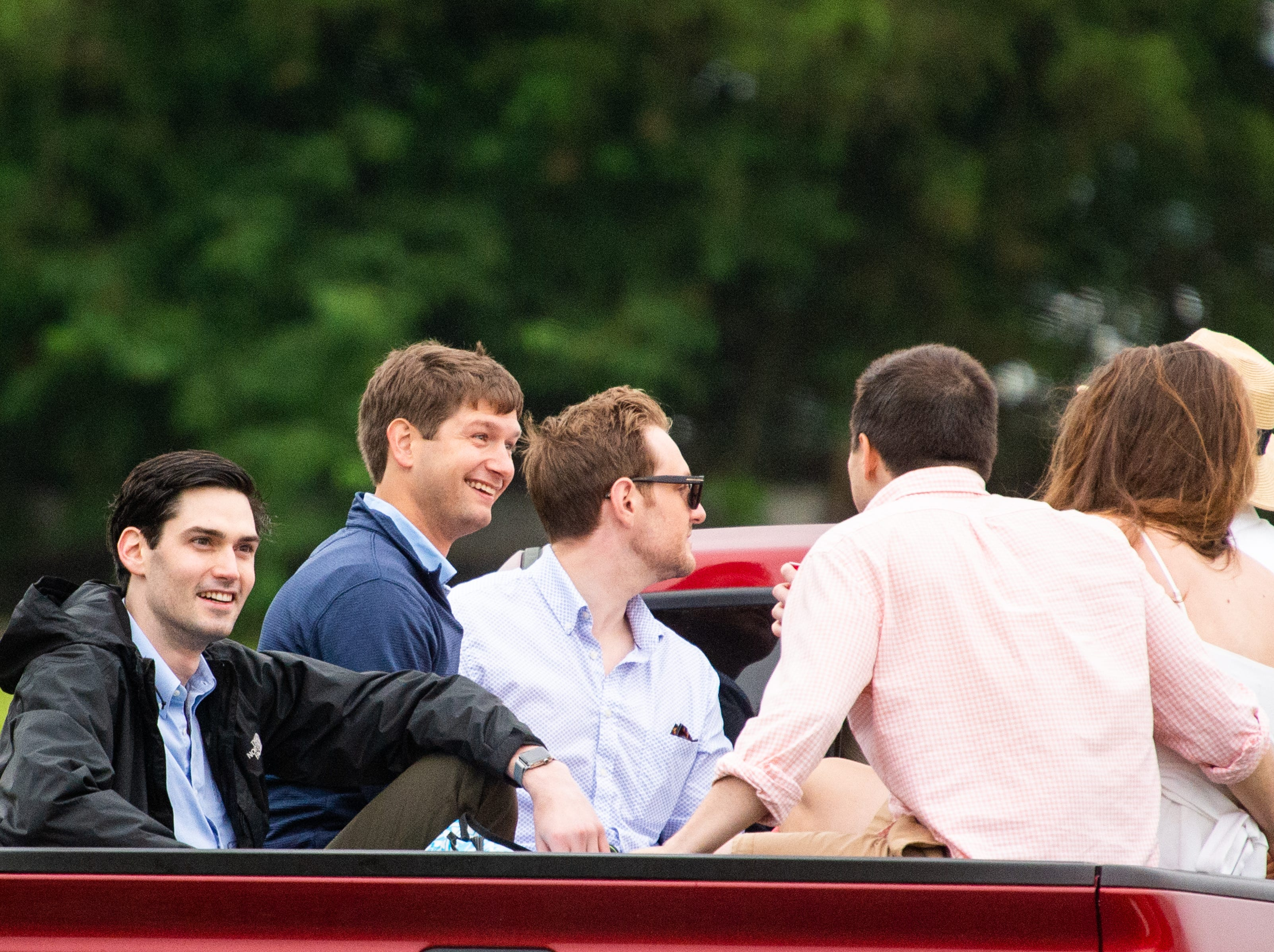 People arrive in the back of a pickup truck during the Iroquois Steeplechase at Percy Warner Park Saturday, May 11, 2019, in Nashville, Tenn.