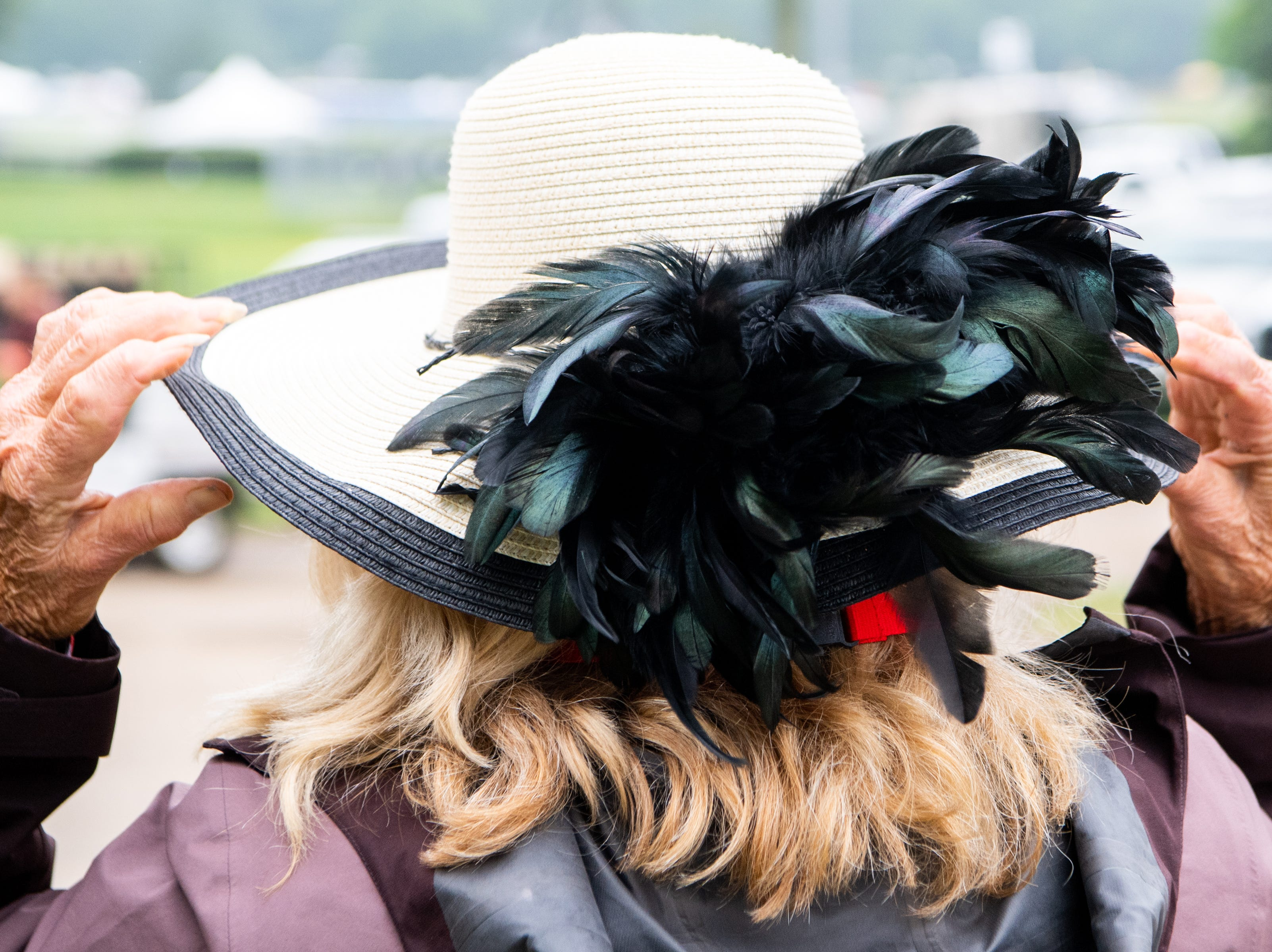 Ann Gayle Hall adjusts her hat during the Iroquois Steeplechase at Percy Warner Park Saturday, May 11, 2019, in Nashville, Tenn.