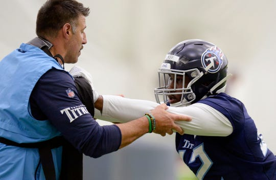 Tennessee Titans coach Mike Vrabel, left, runs a drill with linebacker D'Andre Walker (42) during rookie minicamp Saturday, May 11, 2019.