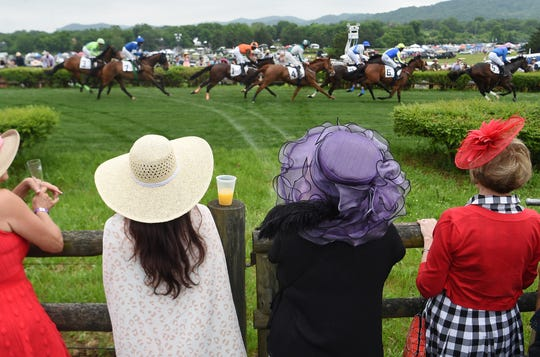 Spectators watch horses race by during the 78th Iroquois Steeplechase at Percy Warner Park in Nashville on Saturday, May 11, 2019.