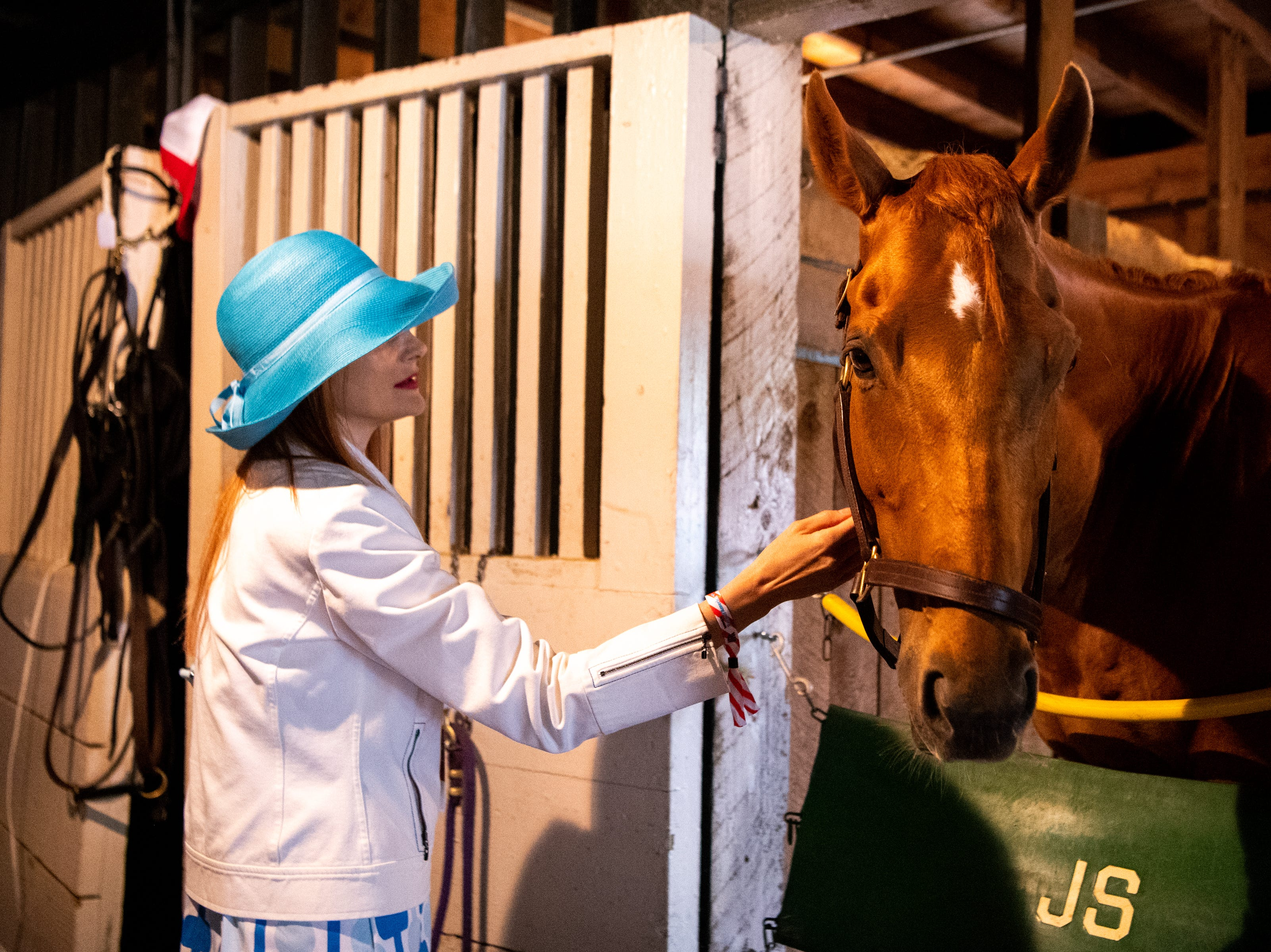 Elizabeth Wild pets a horse in the stables during the Iroquois Steeplechase at Percy Warner Park Saturday, May 11, 2019, in Nashville, Tenn.